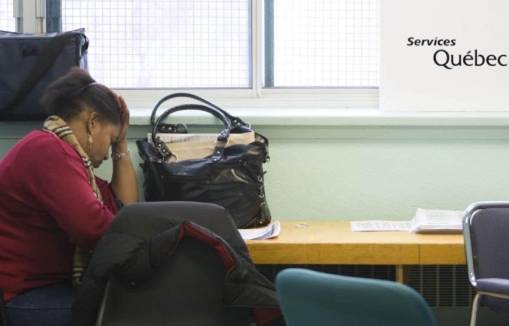 Une Haïtienne remplit un formulaire à la table de Services Québec, à la Maison d'Haïti.