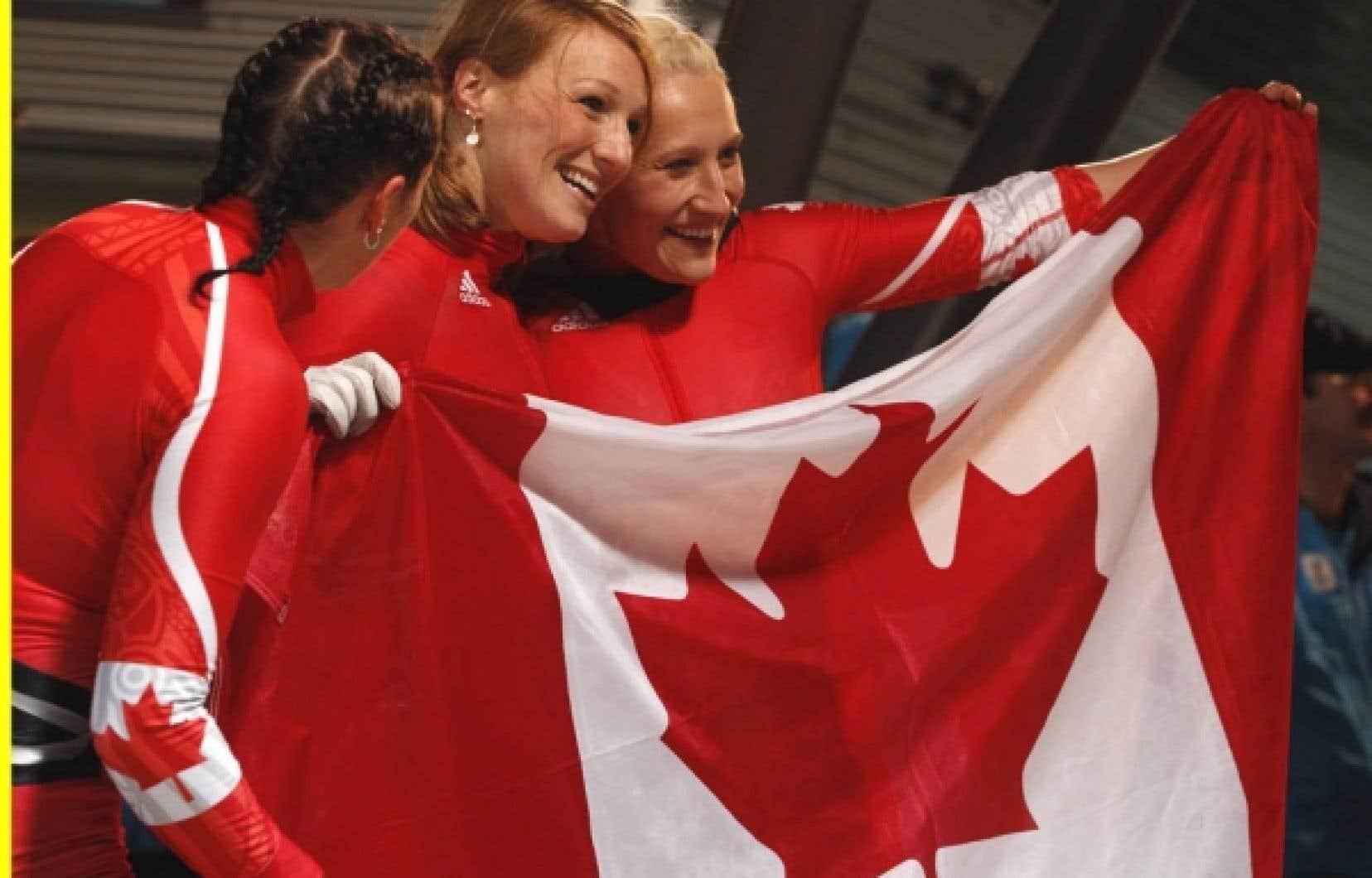 Heather Moyse (au centre), Kaillie Humphries (à droite) et Helen Upperton (à gauche) célèbrent leur podium avec le drapeau canadien.