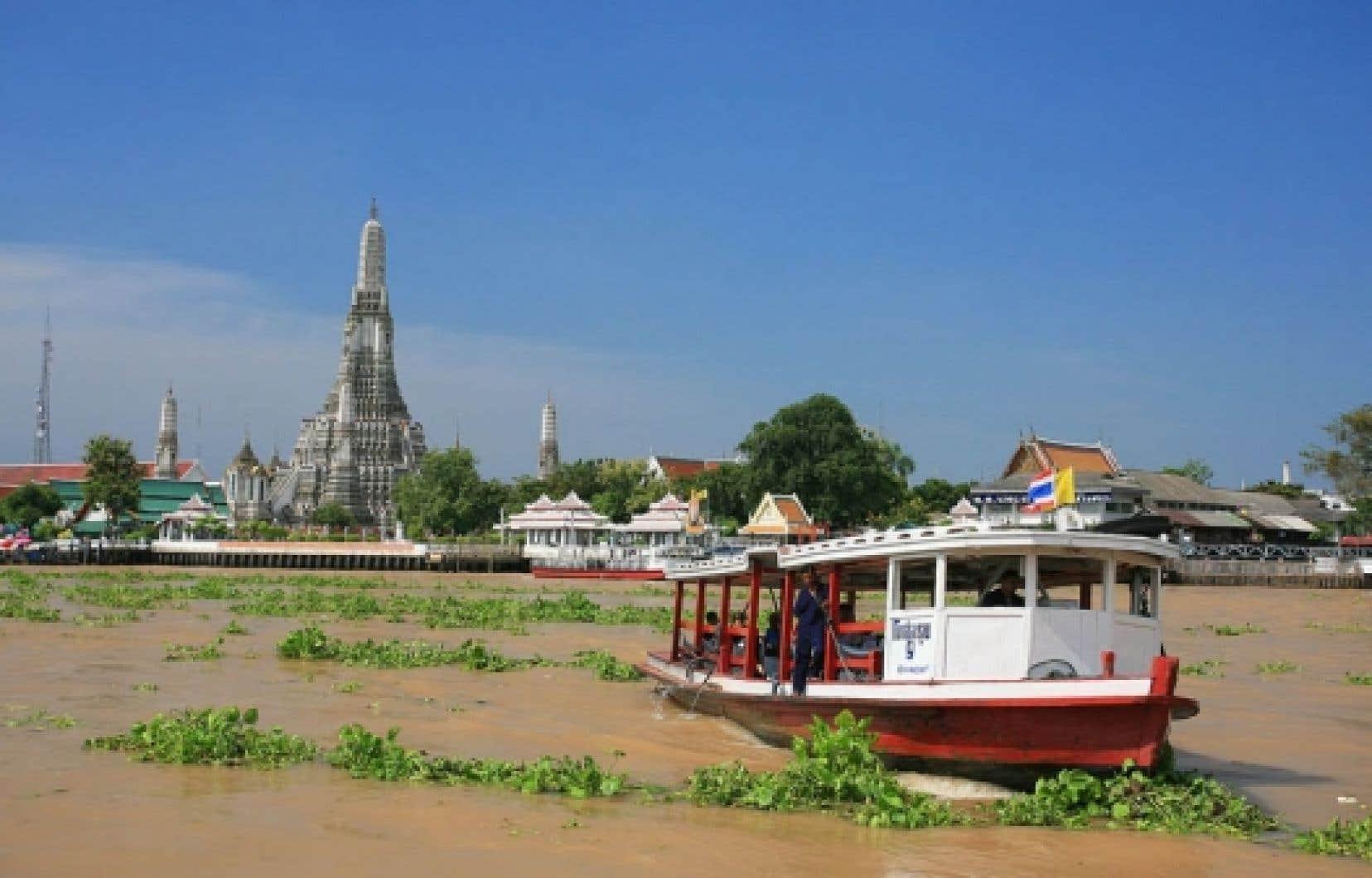 Une modeste embarcation touristique sillonne un grand cours d'eau marécageux en marge du centre de Bangkok. En arrière-plan, Wat Arun, le temple de l'Aube.