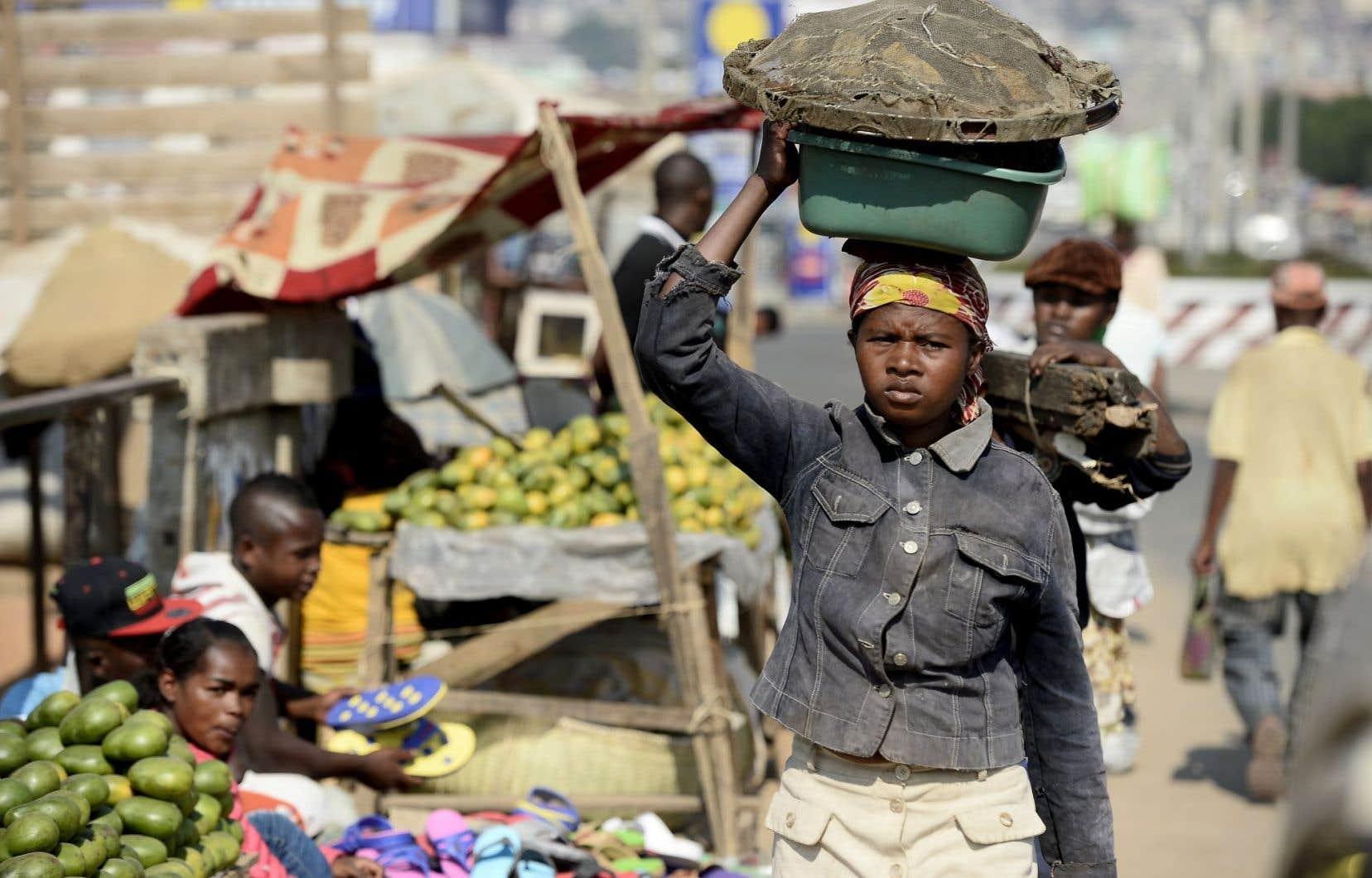 À Antananarivo, une femme déambule dans une rue marchande de la ville.