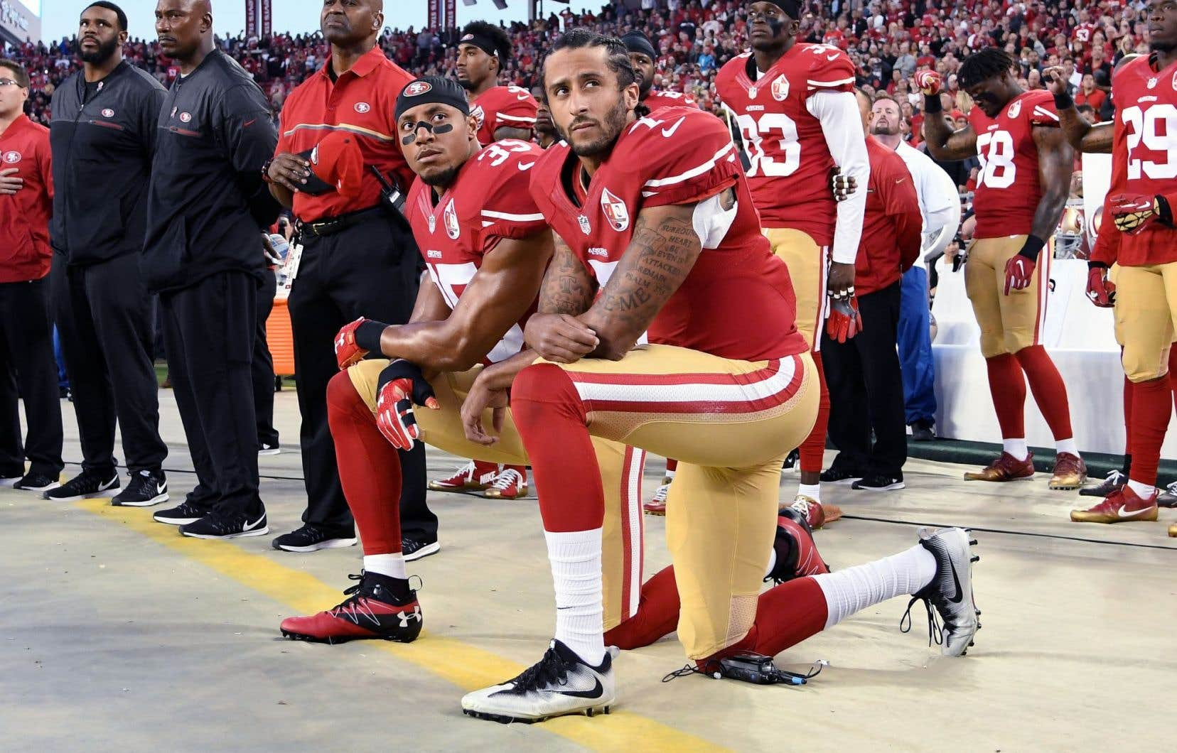 À partir d'août dernier, le quart-arrière des 49ersde San Francisco, Colin Kaepernick (à l'avant-plan), a refusé à plusieurs reprises de se mettre debout pendant l'hymne national précédant un match, comme contre les Rams de Los Angeles en septembre.