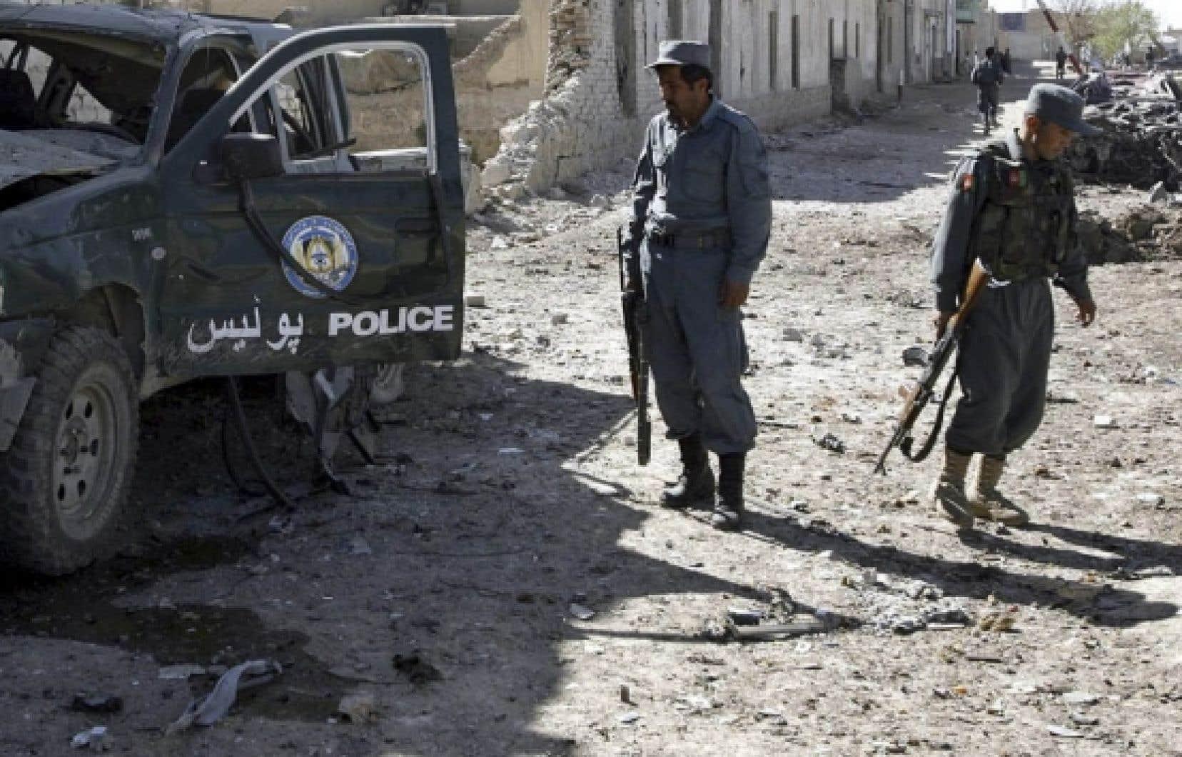 Des policiers afghans examinaient hier les dommages causés par un attentat à Kandahar.