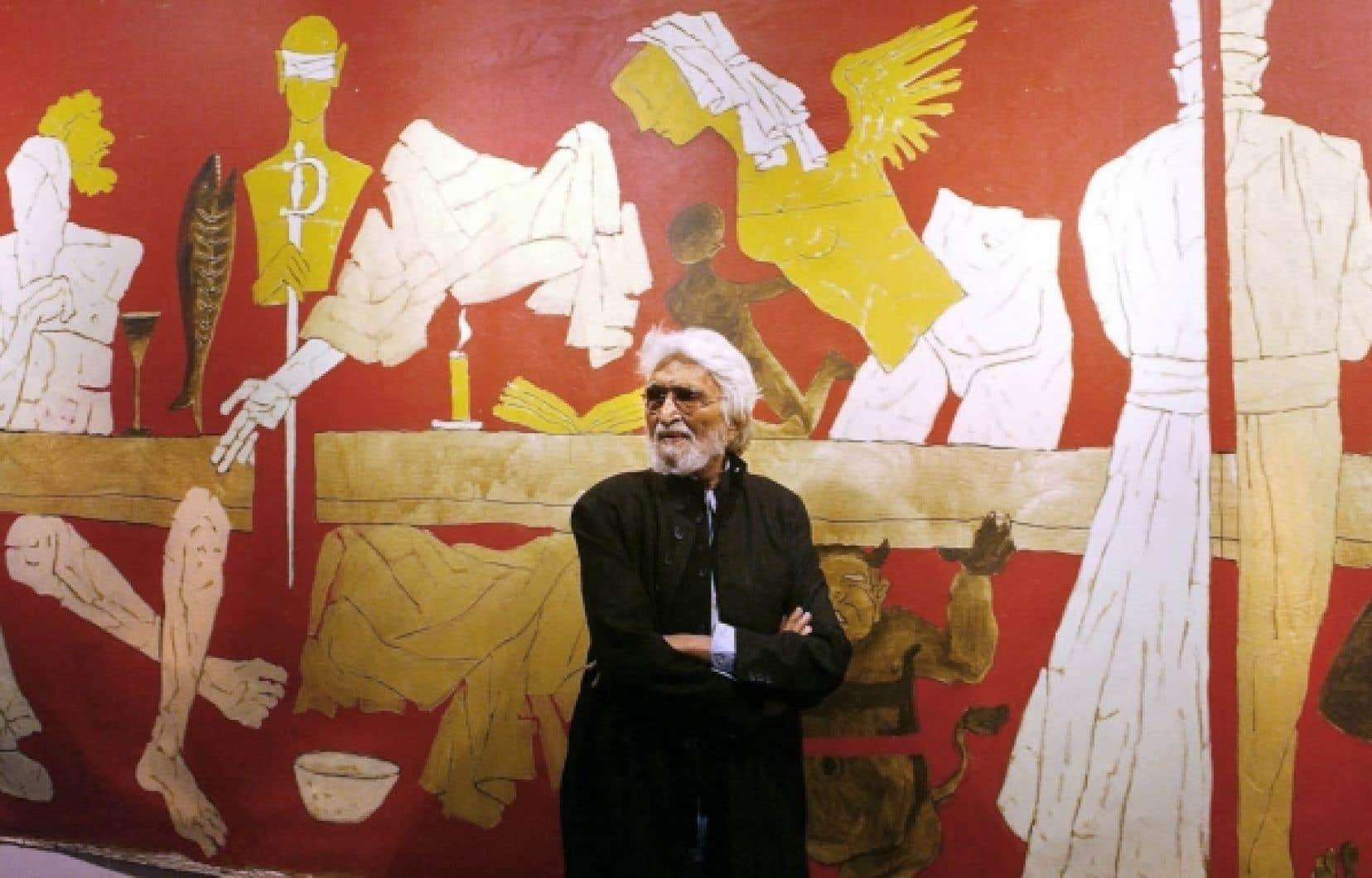 Sur cette photo prise en janvier 2004, l'artiste indien Maqbool Fida Husain pose devant son tableau intitulé Last Supper, lors du vernissage d'une de ses expositions à Londres.