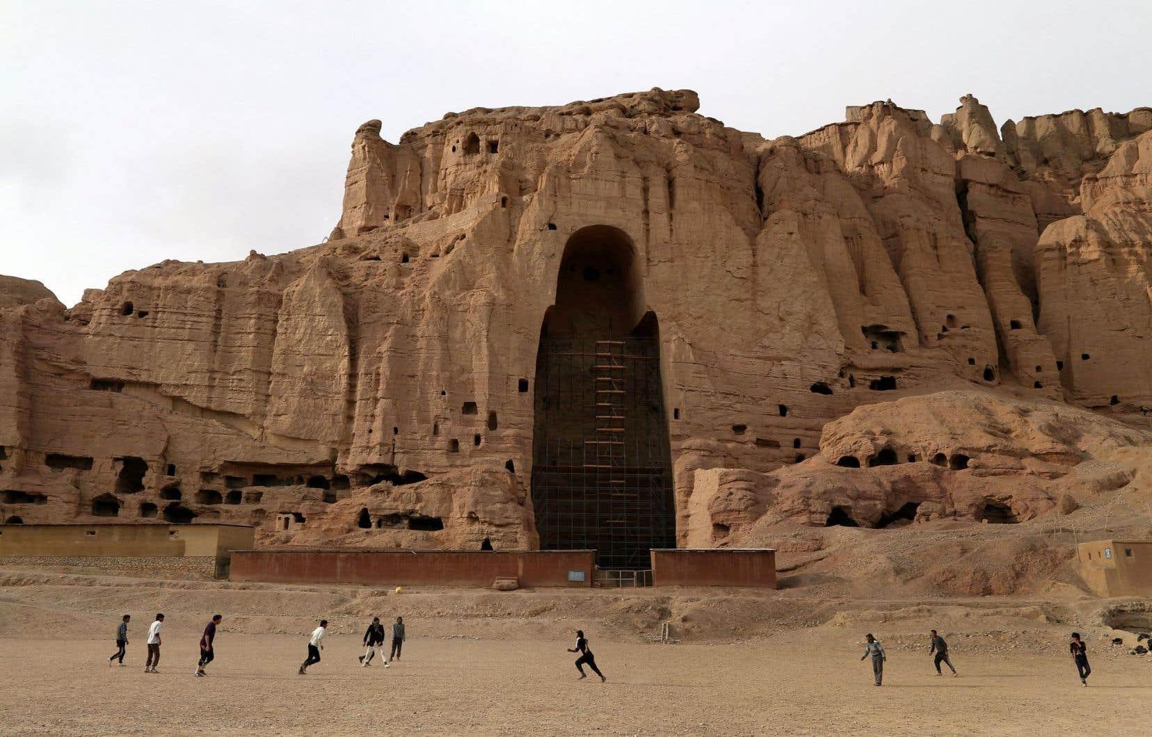 Des enfants afghans jouent au soccer devant les vestiges des bouddhas de Bâmiyân, détruits en mars 2001 par les talibans.