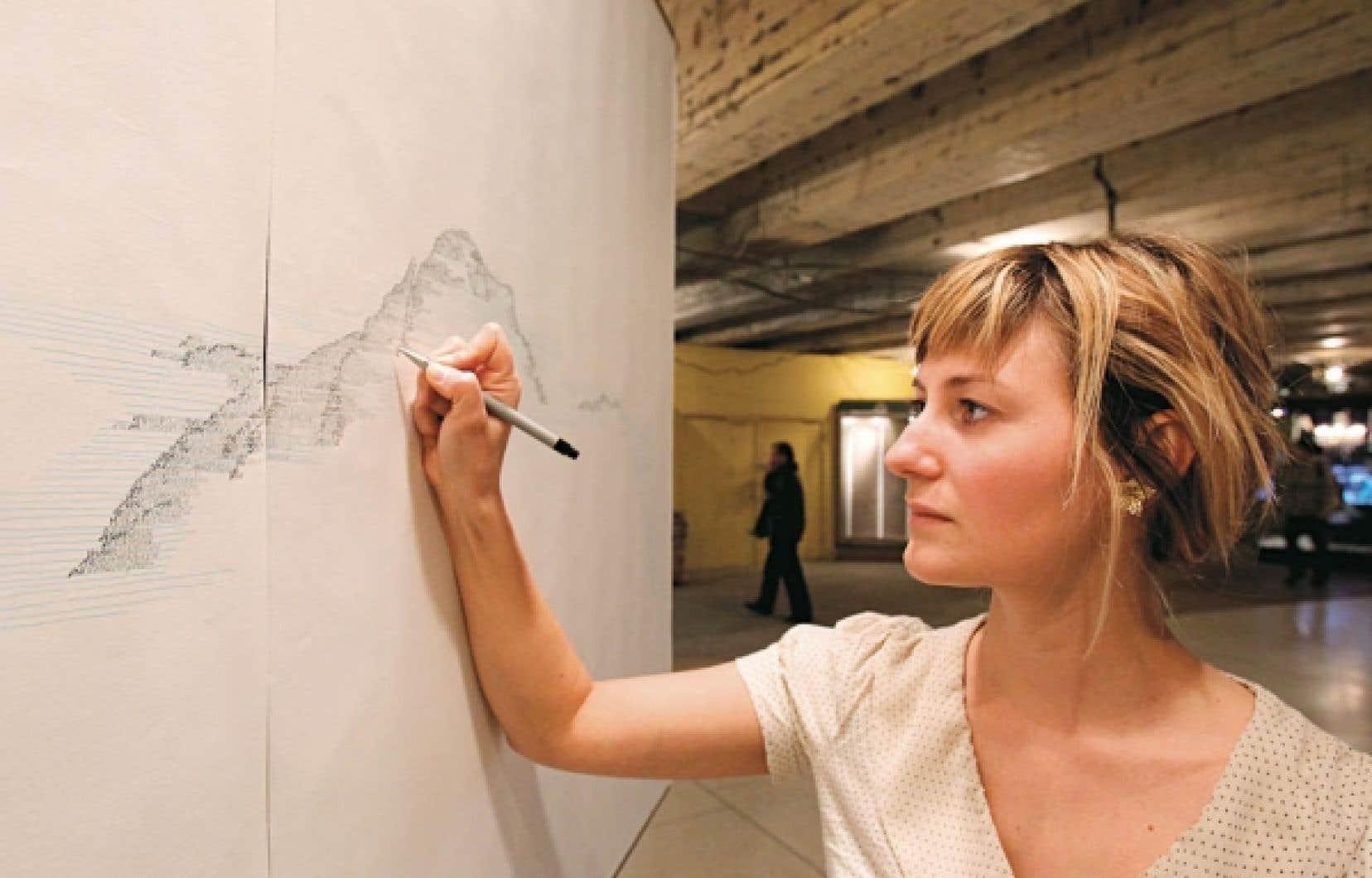 Marie-Michelle Deschamps: c'est elle qu'on voit de dos, ces jours-ci, le nez collé sur trois panneaux blancs. C'est qu'elle dessine au crayon, ou écrit, c'est selon, en très petits caractères.