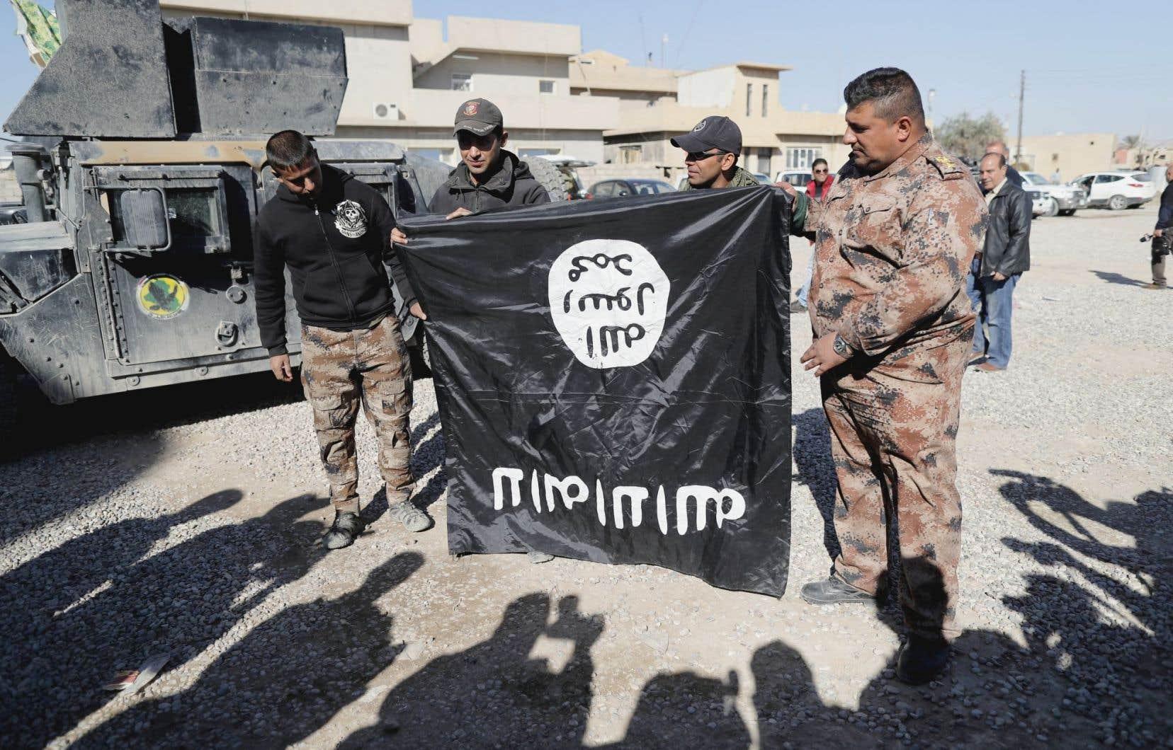 Des soldats irakiens tiennent un drapeau du groupe EI, près de Mossoul.