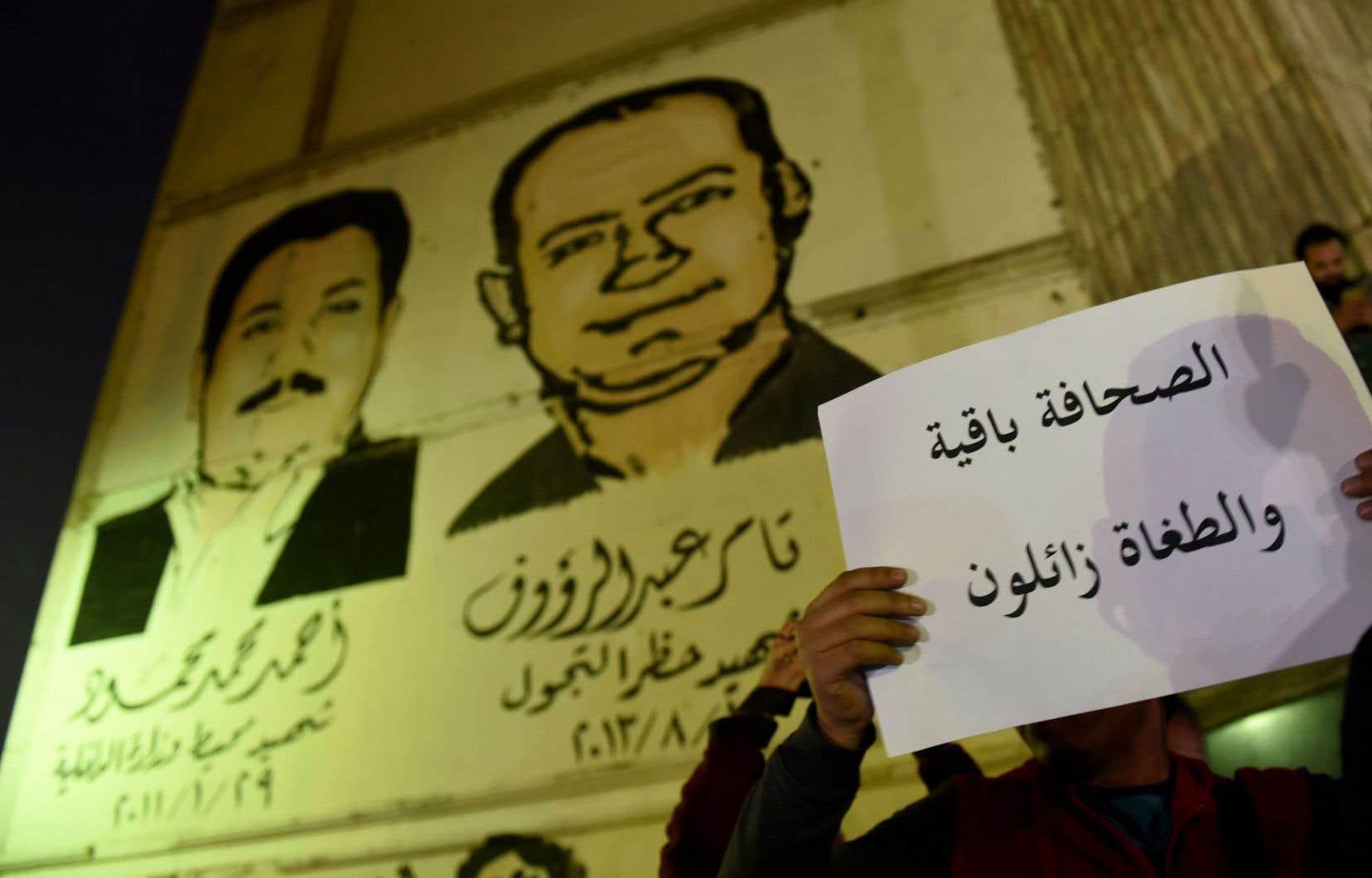 Un journaliste tient une feuille sur laquelle on peut lire «Le journaliste reste et les tyrans sont sur le point de disparaitre», le 19 novembre 2016, au Caire, en Égypte.