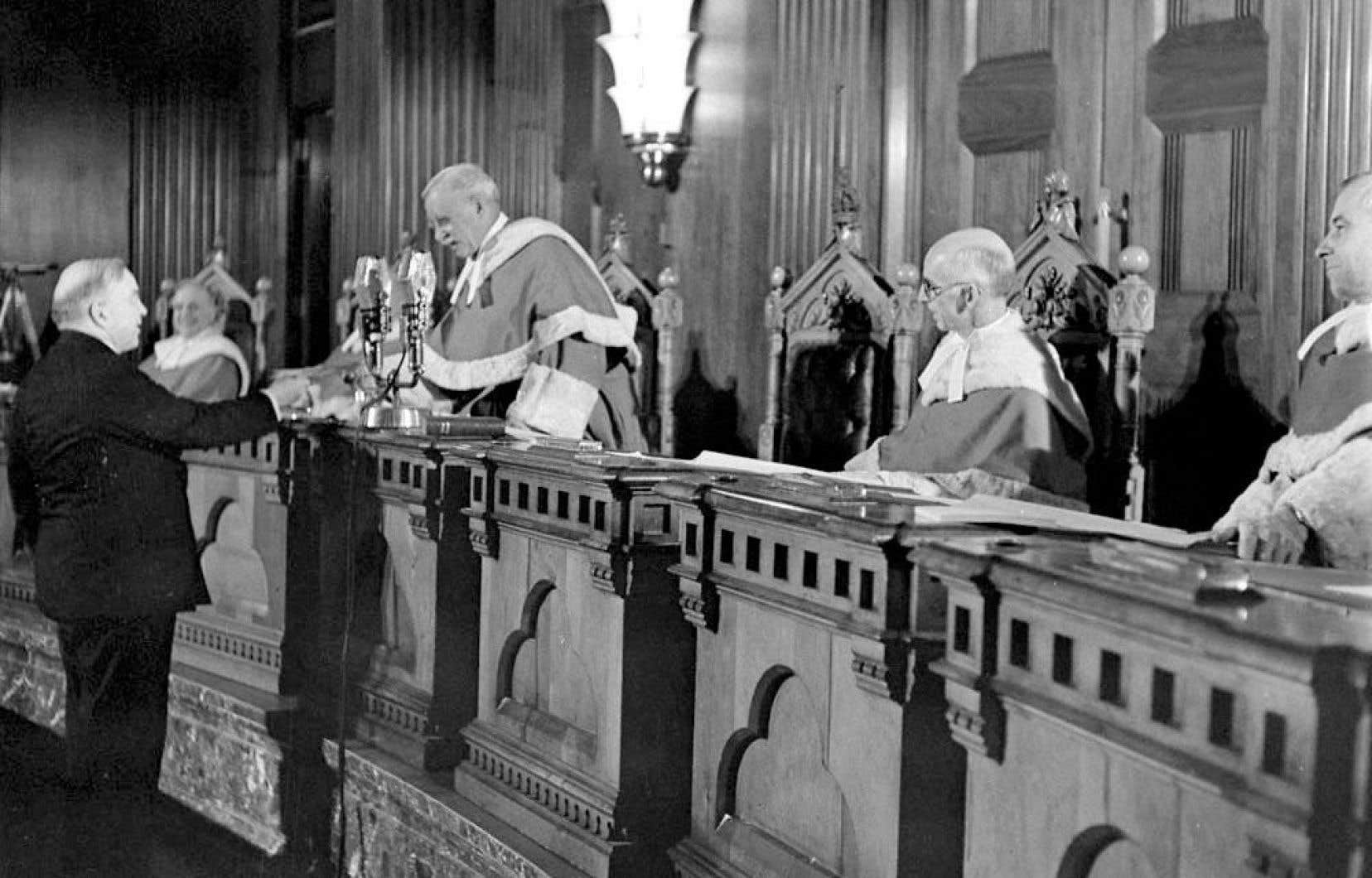 Le juge en chef Thibaudeau Rinfret remet à W. L. Mackenzie King le tout premier certificat de citoyenneté.