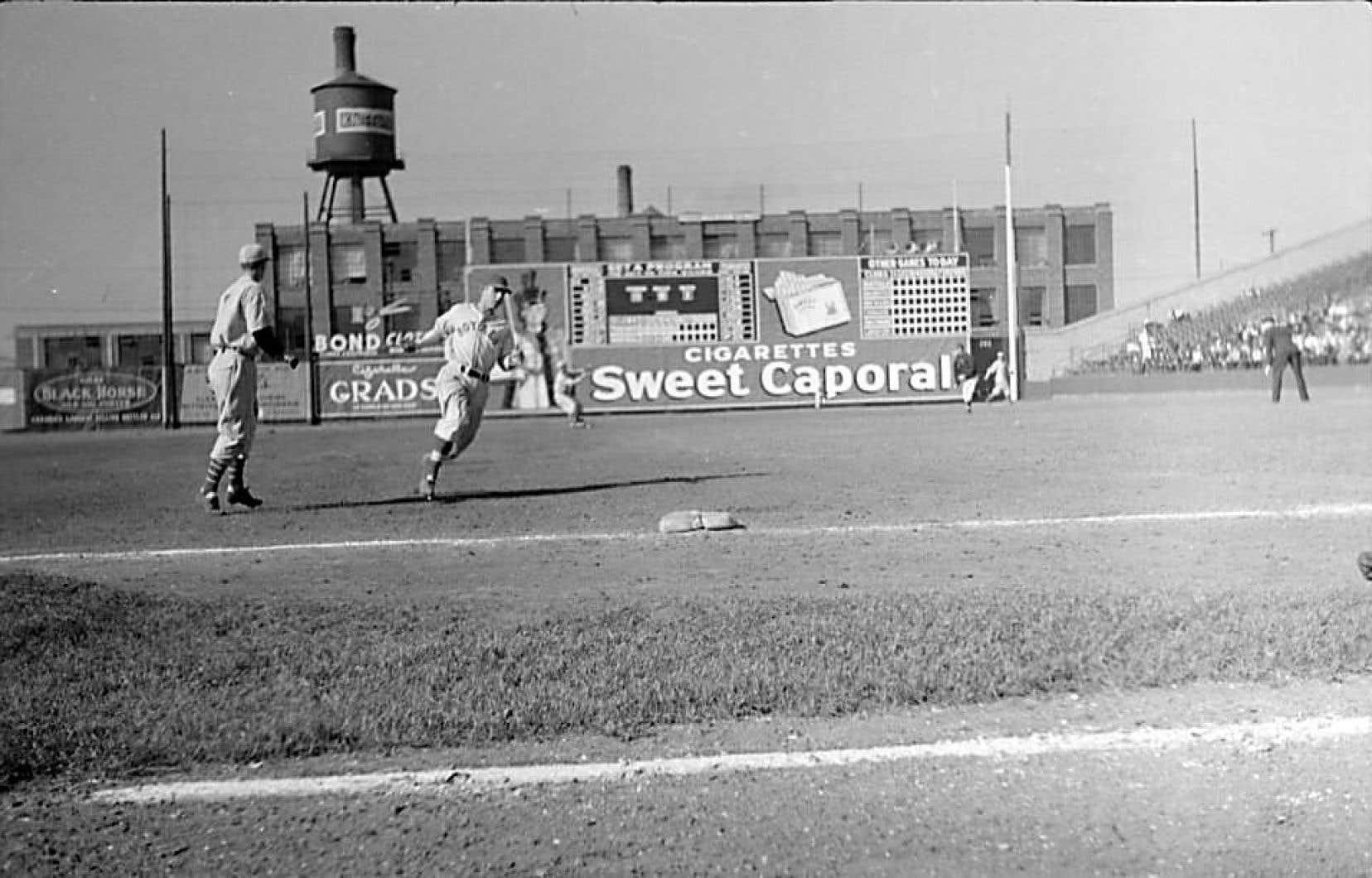 28mai 1937. Le receveur des Royaux Norman Kies s'apprête à contourner le troisième but lors d'un match de baseball opposant l'équipe montréalaise aux «Toronto Maple Leafs», au stade De Lorimier à Montréal.