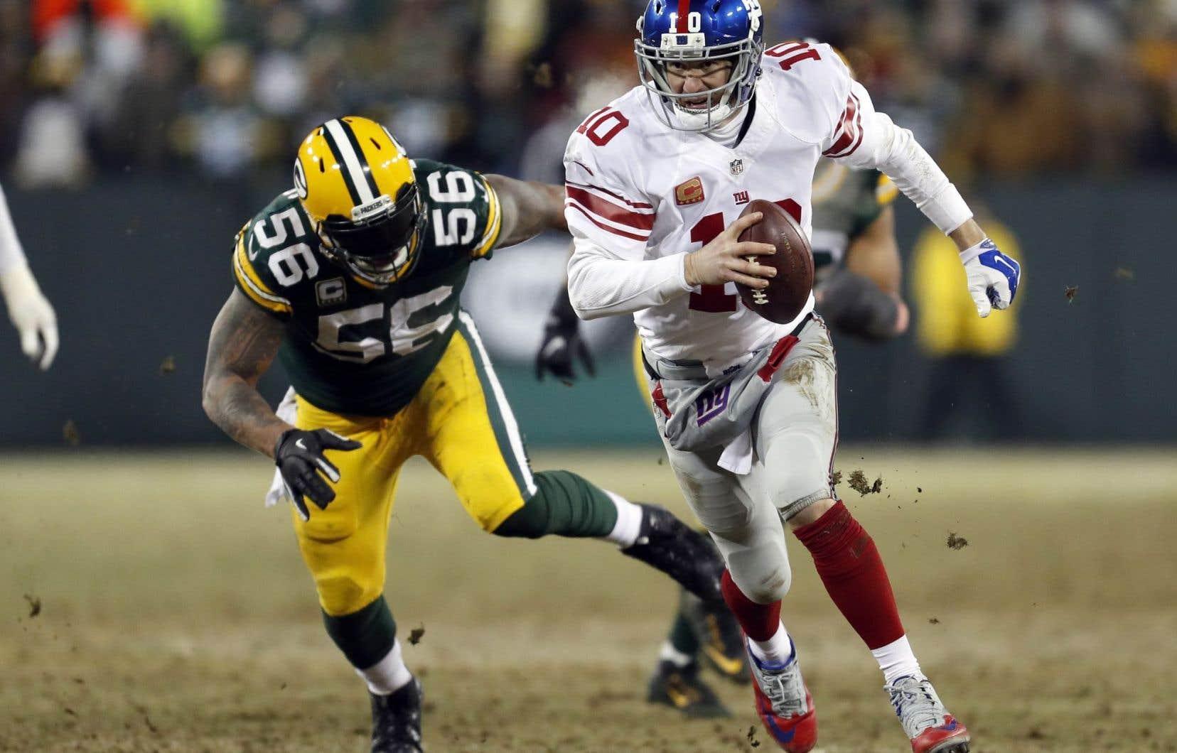 Le quart-arrière des Giants de New York Eli Manning (10) et le secondeur extérieur des Packers de Green Bay Julius Peppers (56).