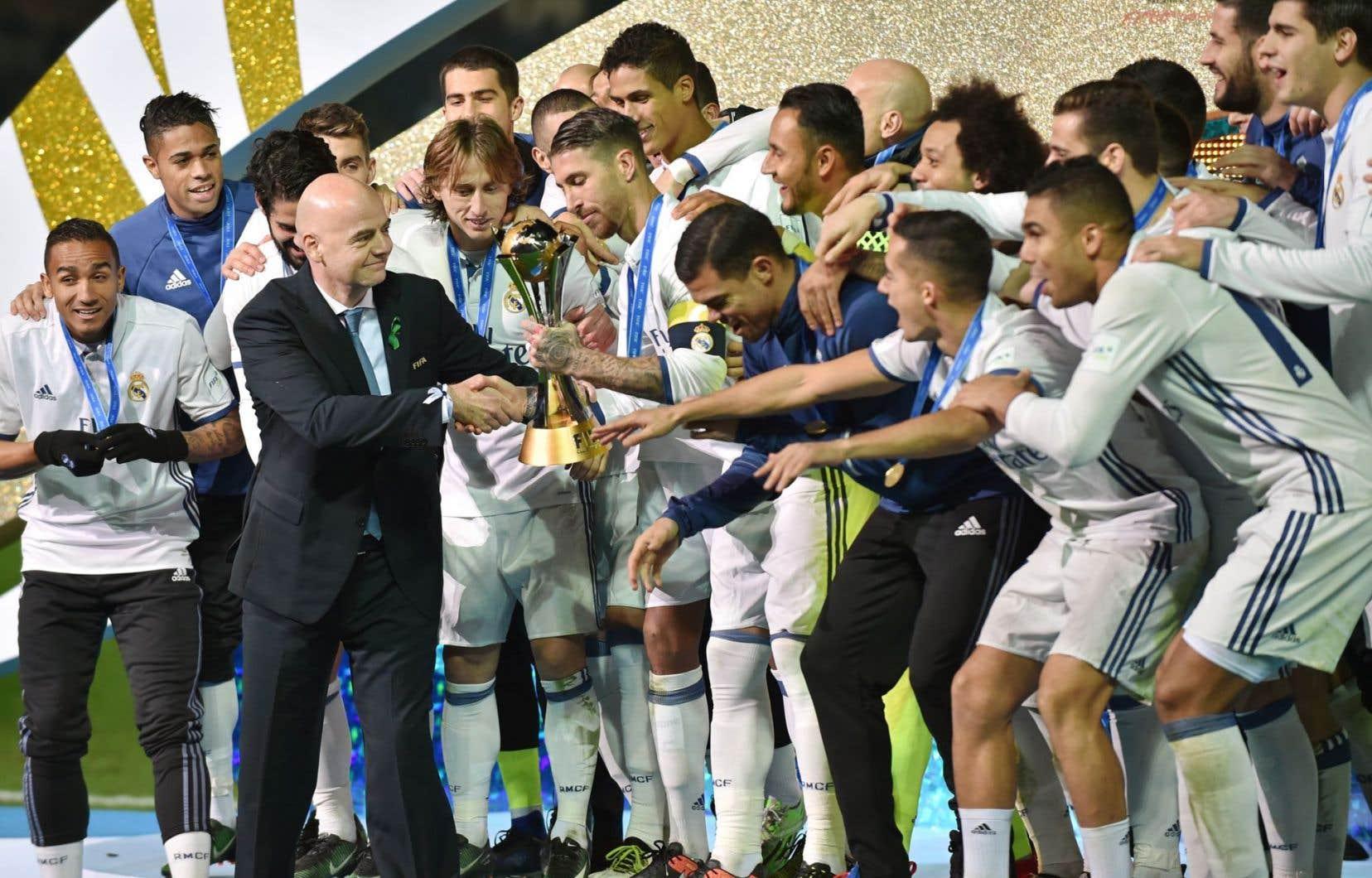 Le président de la FIFA, Gianni Infantino, tend le trophée du Mondial des clubs de la FIFA aux joueurs du Real Madrid dans la ville japonaise de Yokohama le 18 décembre 2016.