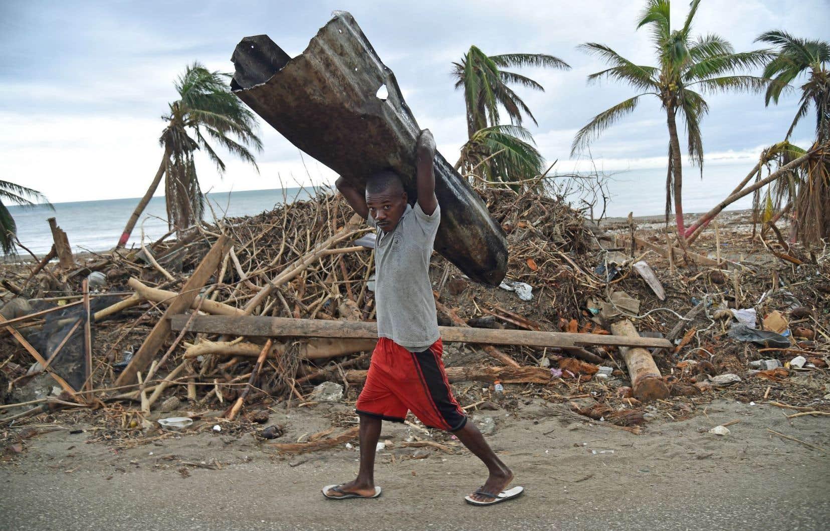 Un jeune homme transporte des matériaux pour réparer sa maison endommagée après le passage de l'ouragan Matthew, en Haïti.