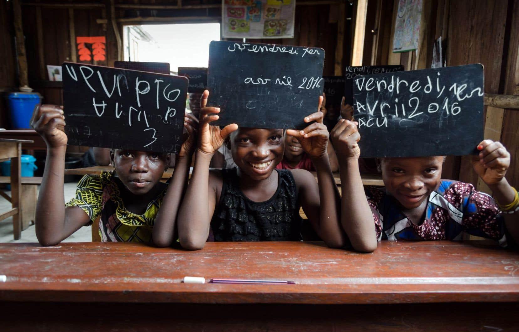 Agathe (8 ans), Rosine (11 ans) et Lucresse (7 ans), qui ne savaient ni lire ni écrire lorsqu'elles ont commencé à étudier grâce au projet Assovie, présentent fièrement leur ardoise, sur laquelle elles ont copié la date du jour.