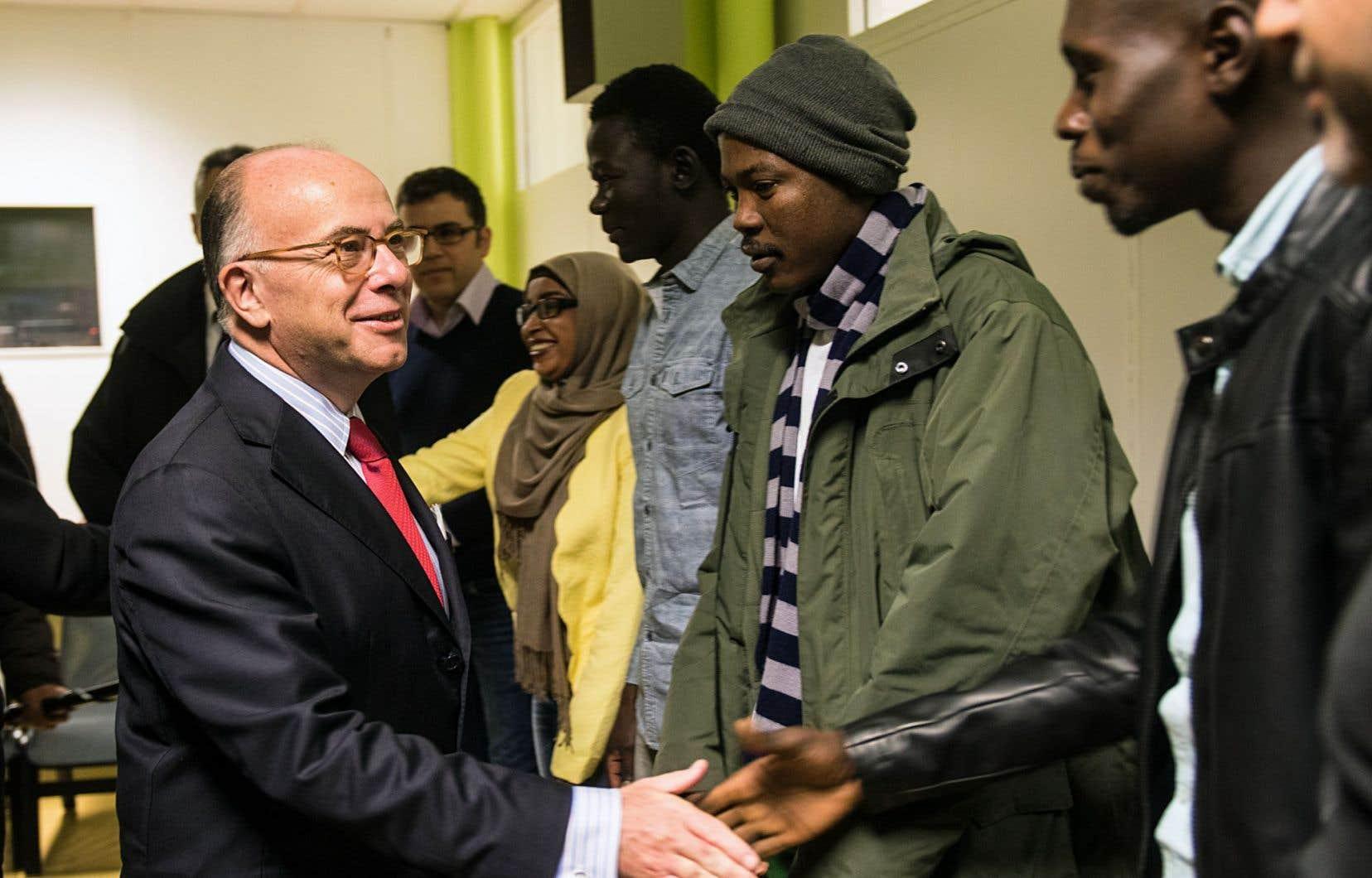 Le ministre français de l'Intérieur, Bernard Cazeneuve, et d'anciens migrants de la «Jungle de Calais»