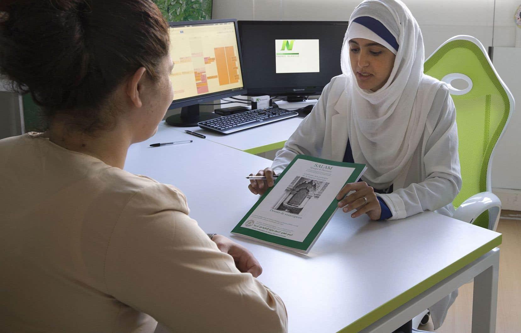 Une employée d'une agence de banque islamique montre une brochure à une de ses clientes.