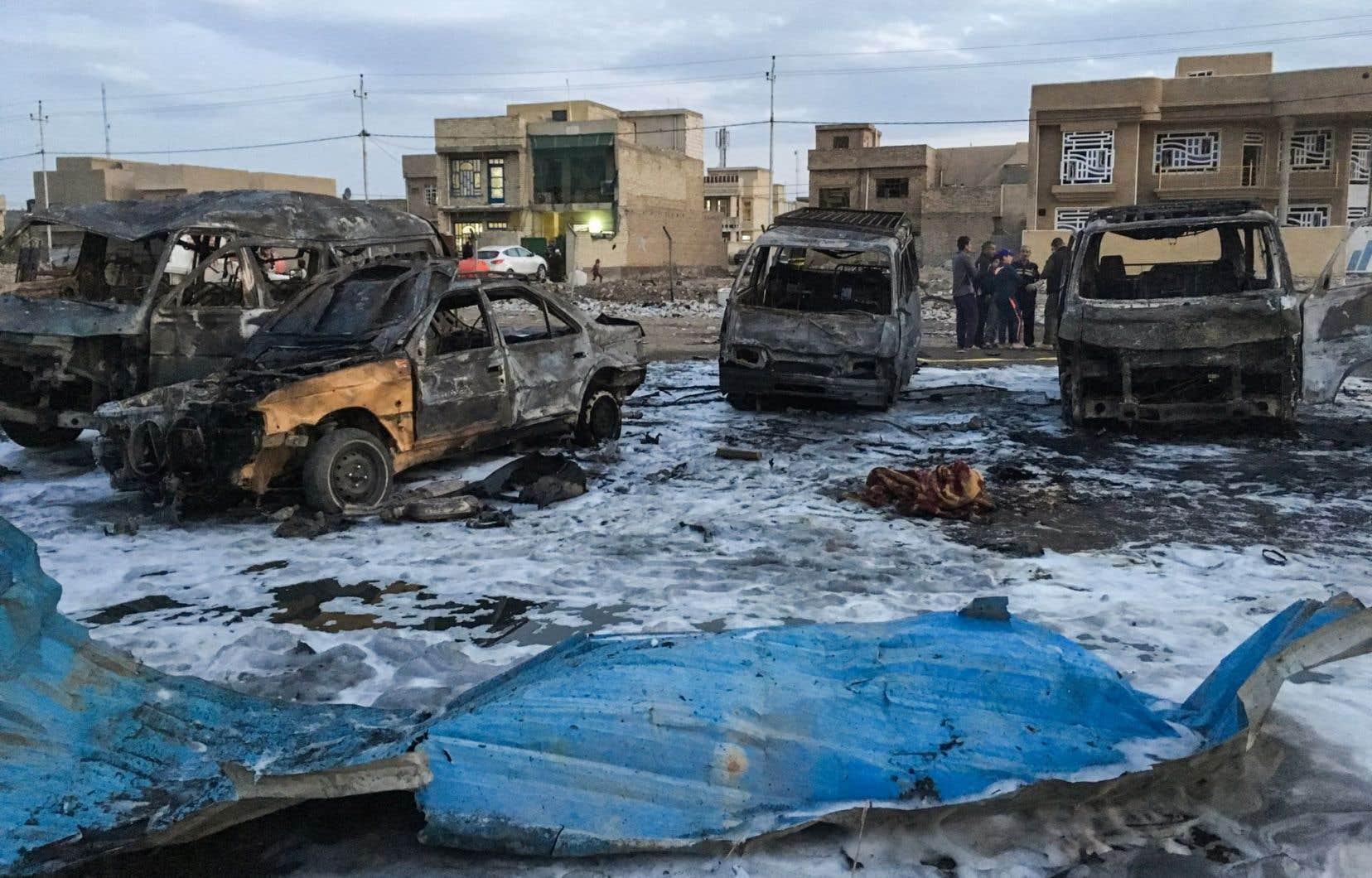 Une photo prise avec un téléphone mobile montre des véhicules brûlés sur les lieux d'une explosion causée par une voiture piégée. Des dizaines de personnes ont été tuées dans un marché de voitures d'occasion dans le sud de Bagdad.