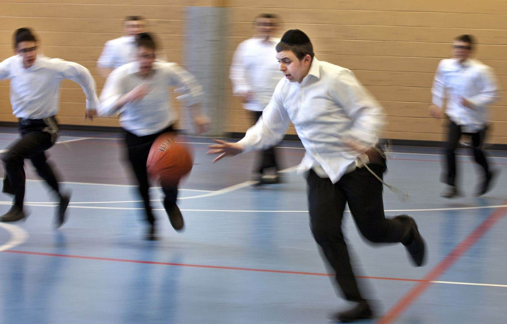 Portant l'uniforme réglementaire — chemise blanche, pantalons noirs et tzitzit —, des jeunes de la Yeshiva Gedola jouent au basket-ball sur l'heure du dîner.