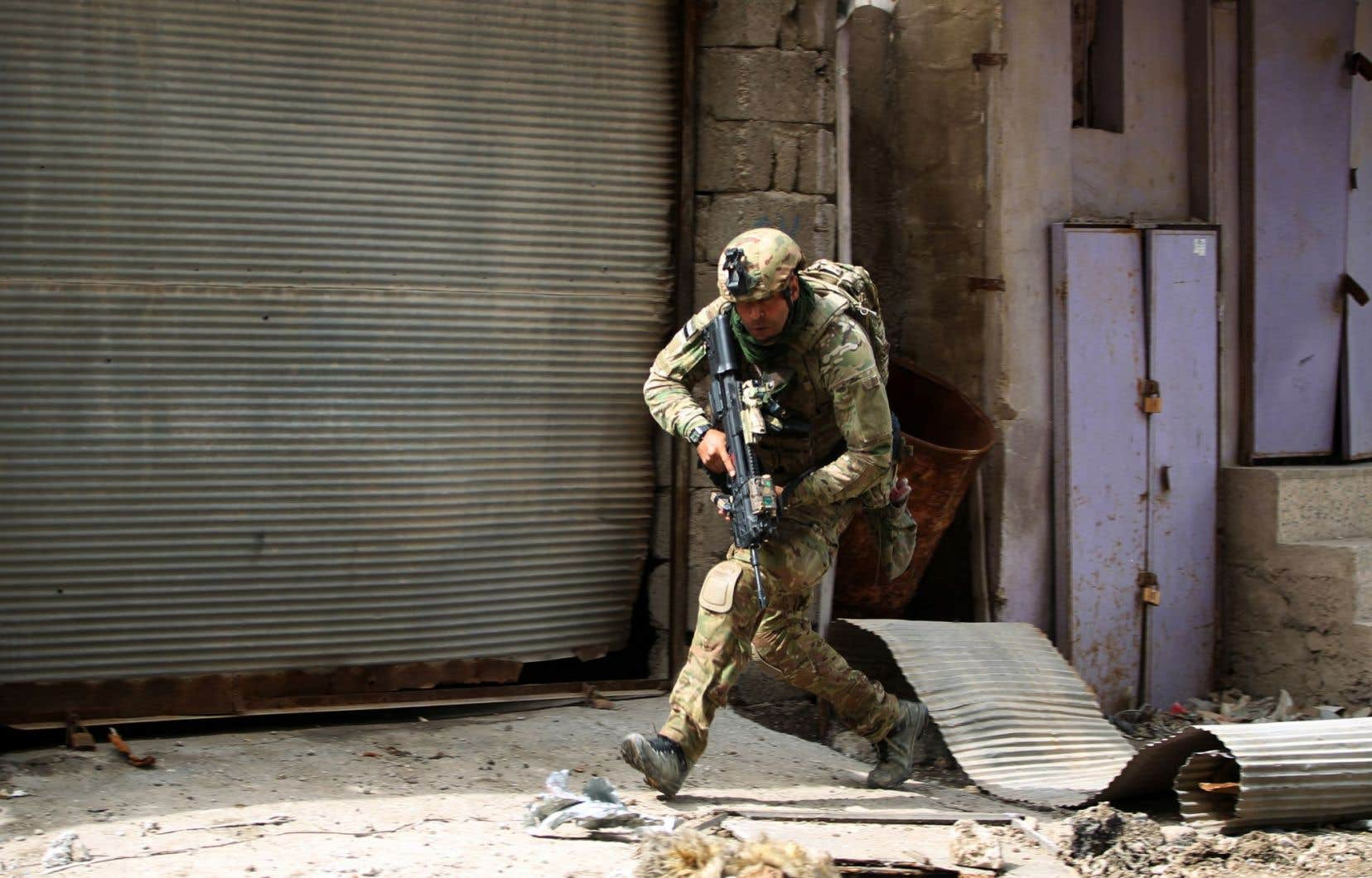 Un membre des forces irakiennes court se mettre à couvert lors de leur avancée dans la vieille ville de l'ouest de Mossoul.