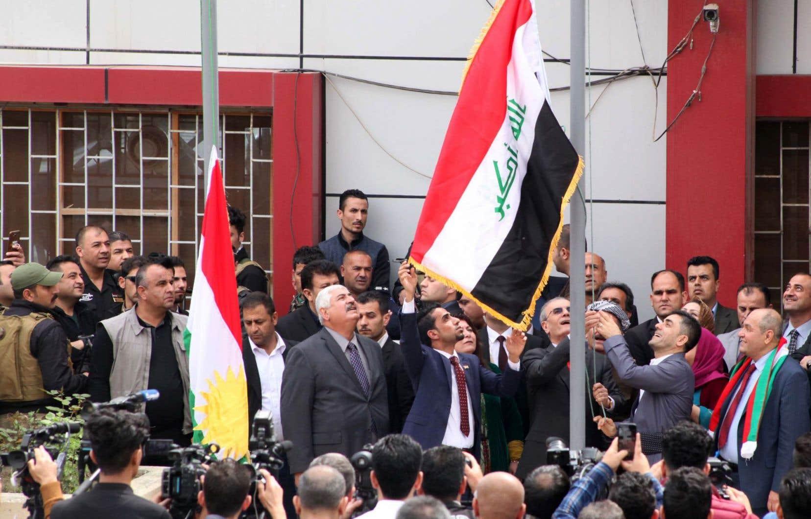 Le gouverneur provincial de Kirkuk, Najim al-Din Karim, hisse le drapeau irakien à côté du drapeau kurde sur un immeuble gouvernemental situé dans la ville irakienne du Kirkouk, le 28 mars 2017.