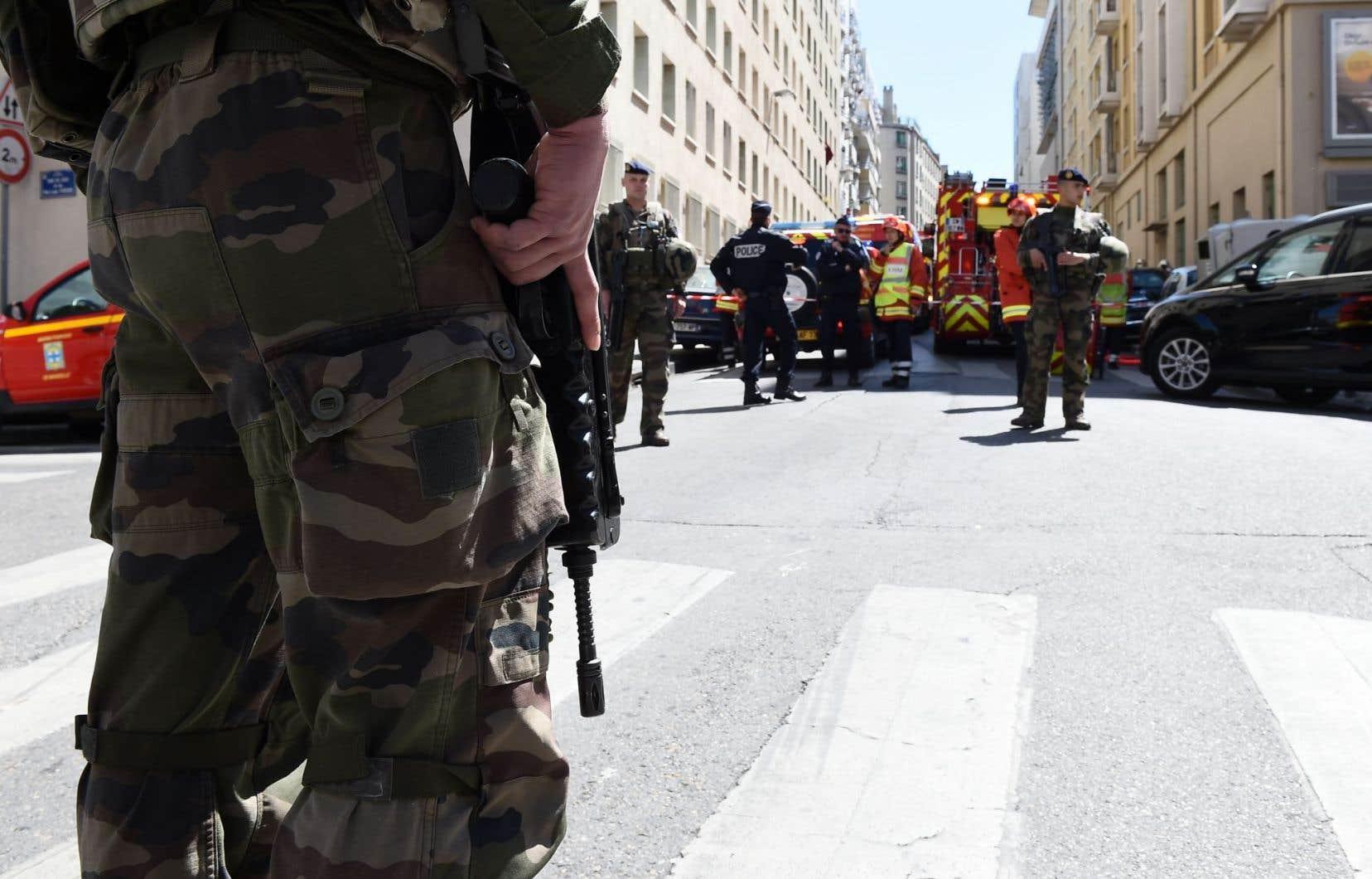 Des soldats français, des policiers et des pompiers sont aperçus sur le site d'une fouille policière à la maison d'un des deux hommes arrêtés.