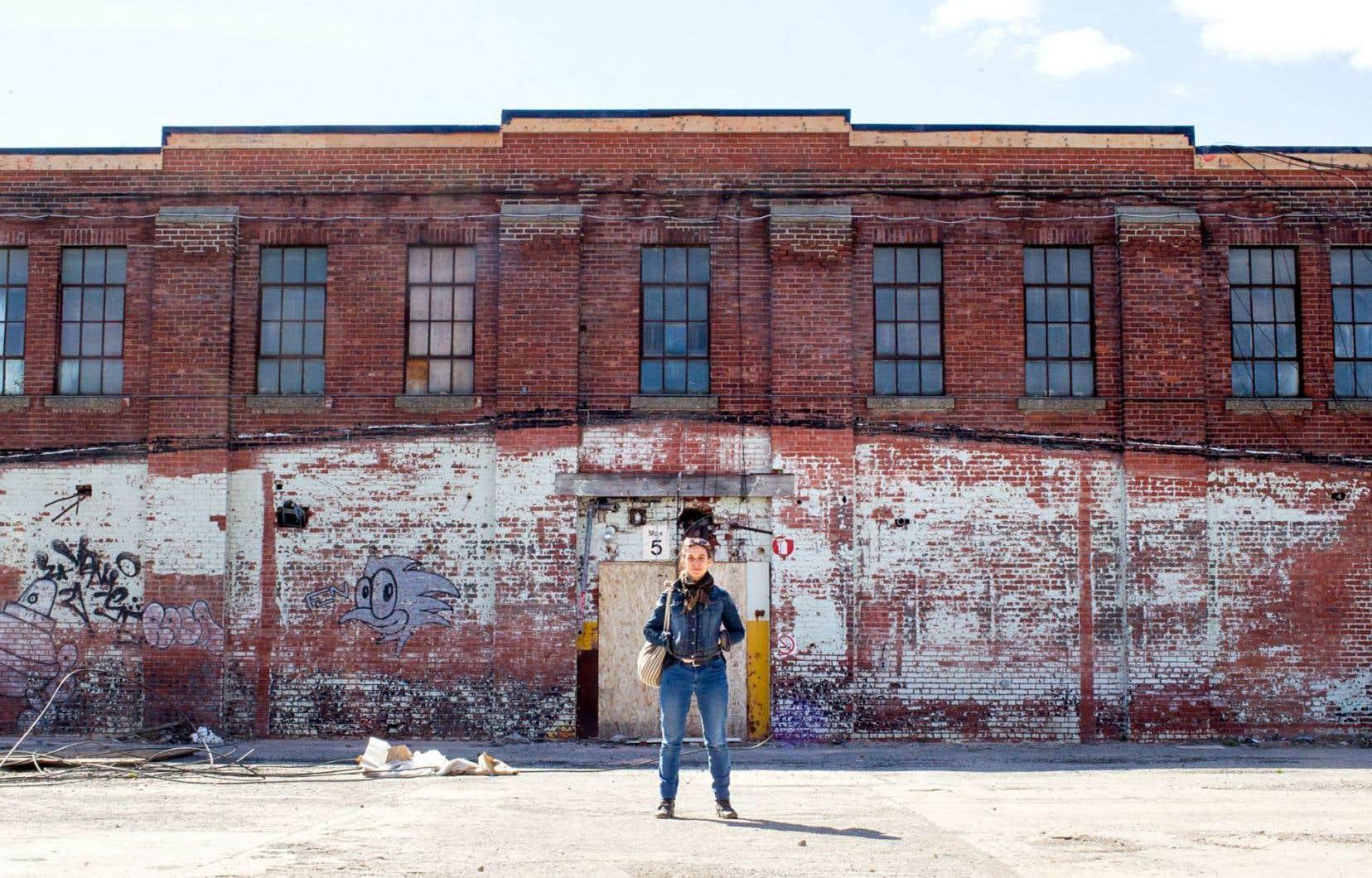 Judith Cayer, chargée de projet, pose devant le Bâtiment 7.