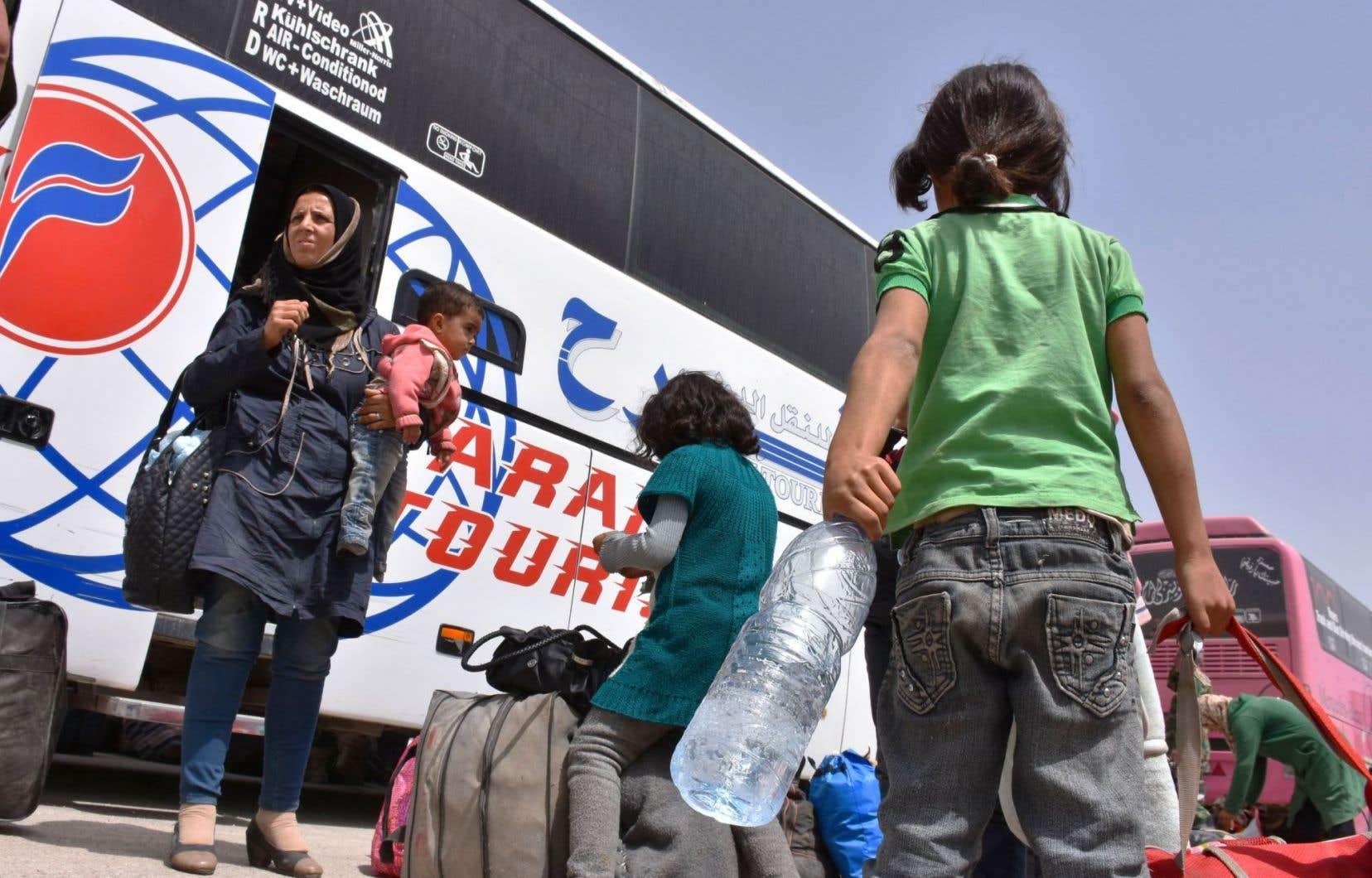 Des habitants des villes de Foua et Kafraya, assiégées par le gouvernement, arrivent à Jibrin, dans la banlieue d'Alep.