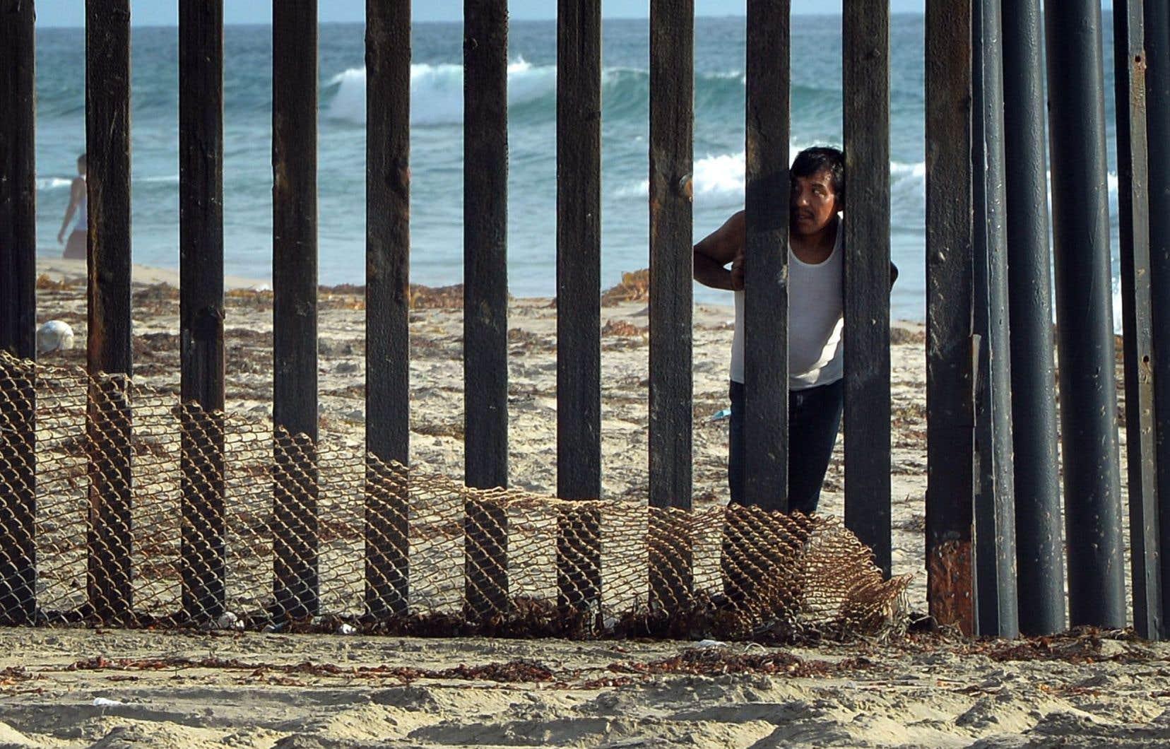 Un homme regarde vers les États-Unis depuis le Mexique dans la région de San Diego, en Californie.