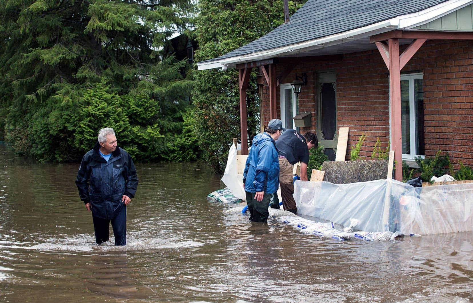 Des parois de sacs de sable et de matériaux de construction divers ont été aménagées devant plusieurs résidences inondées, dont celle-ci, à L'Île-Bizard.