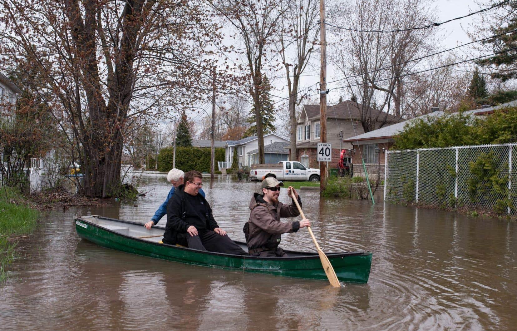 Des résidents de Pierrefonds circulaient en canot dans les rues inondées, dimanche.