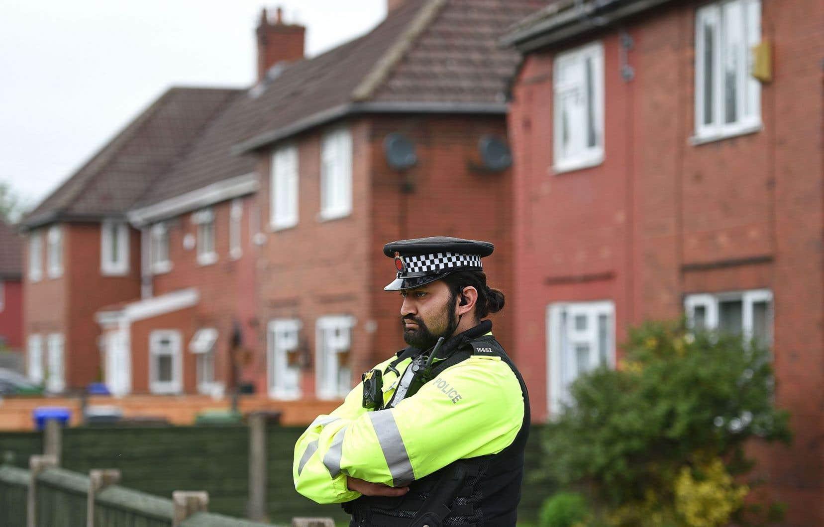 Un officier de police monte la garde devant une résidence en banlieue de Manchester où le suspect Salman Abedi aurait demeuré jusqu'à l'an dernier.