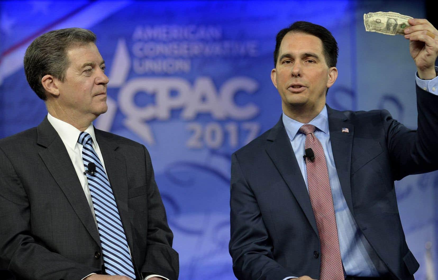 En 2012, le gouverneur du Kansas, Sam Brownback (à gauche), a administré une «piqûre d'adrénaline dans le cœur de l'économie» locale de cet État ultraconservateur du Midwest.