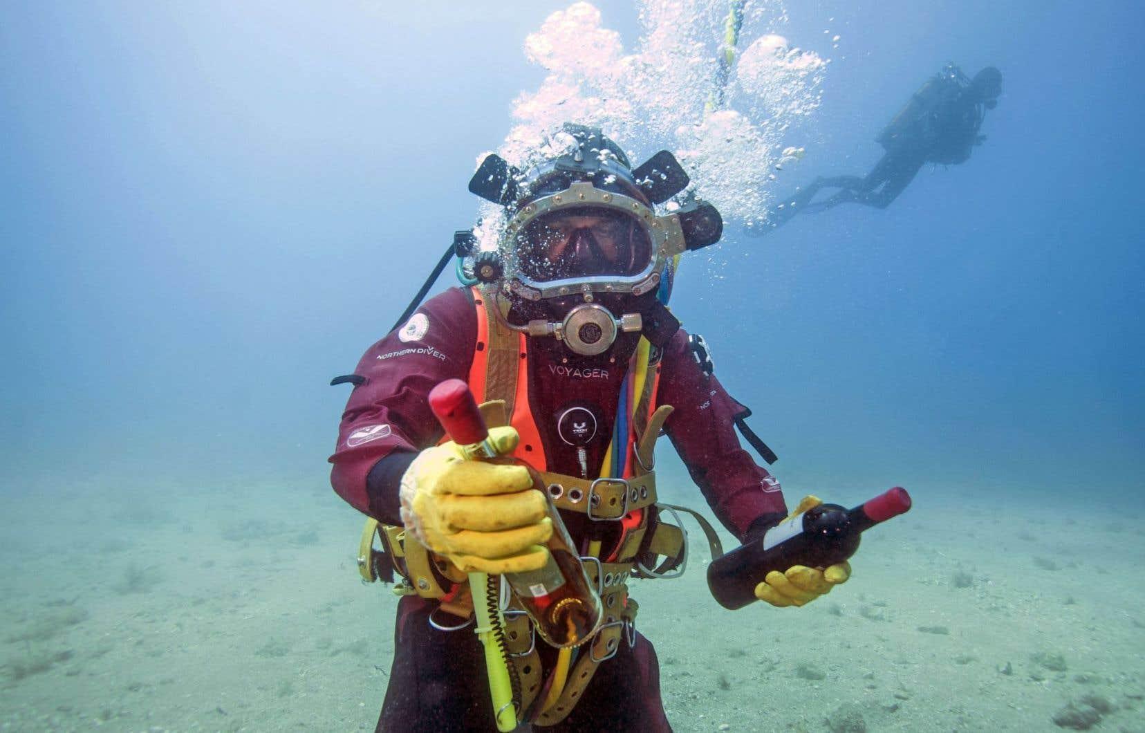 Un plongeur montre des bouteilles repérées dans un cellier en mer Méditerranée. L'expérience vise à évaluer les effets de la maturation des vins de Bandol enfouis sous l'eau pendant un an.