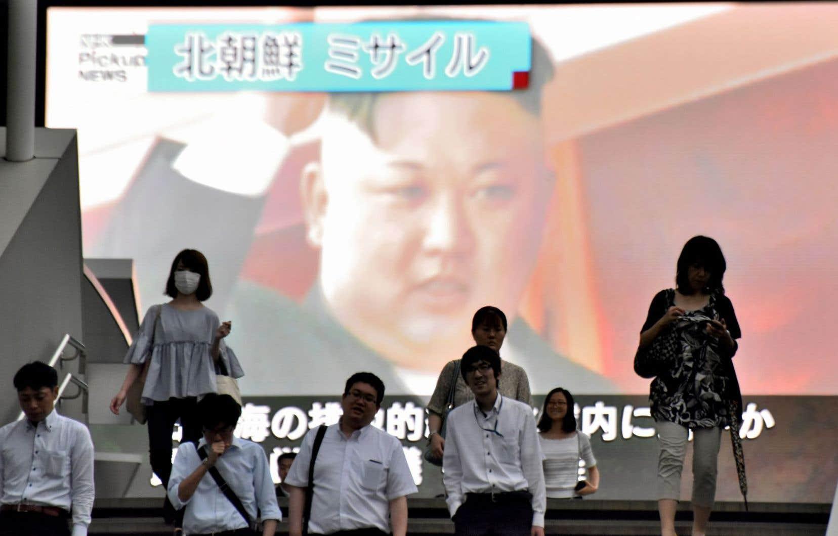 Des piétons passent devant un écran géant à Tokyo sur lequel sont diffusées des images du leader nord-coréen, Kim Jong-un, après un nouveau tir de missile le 4 juillet.