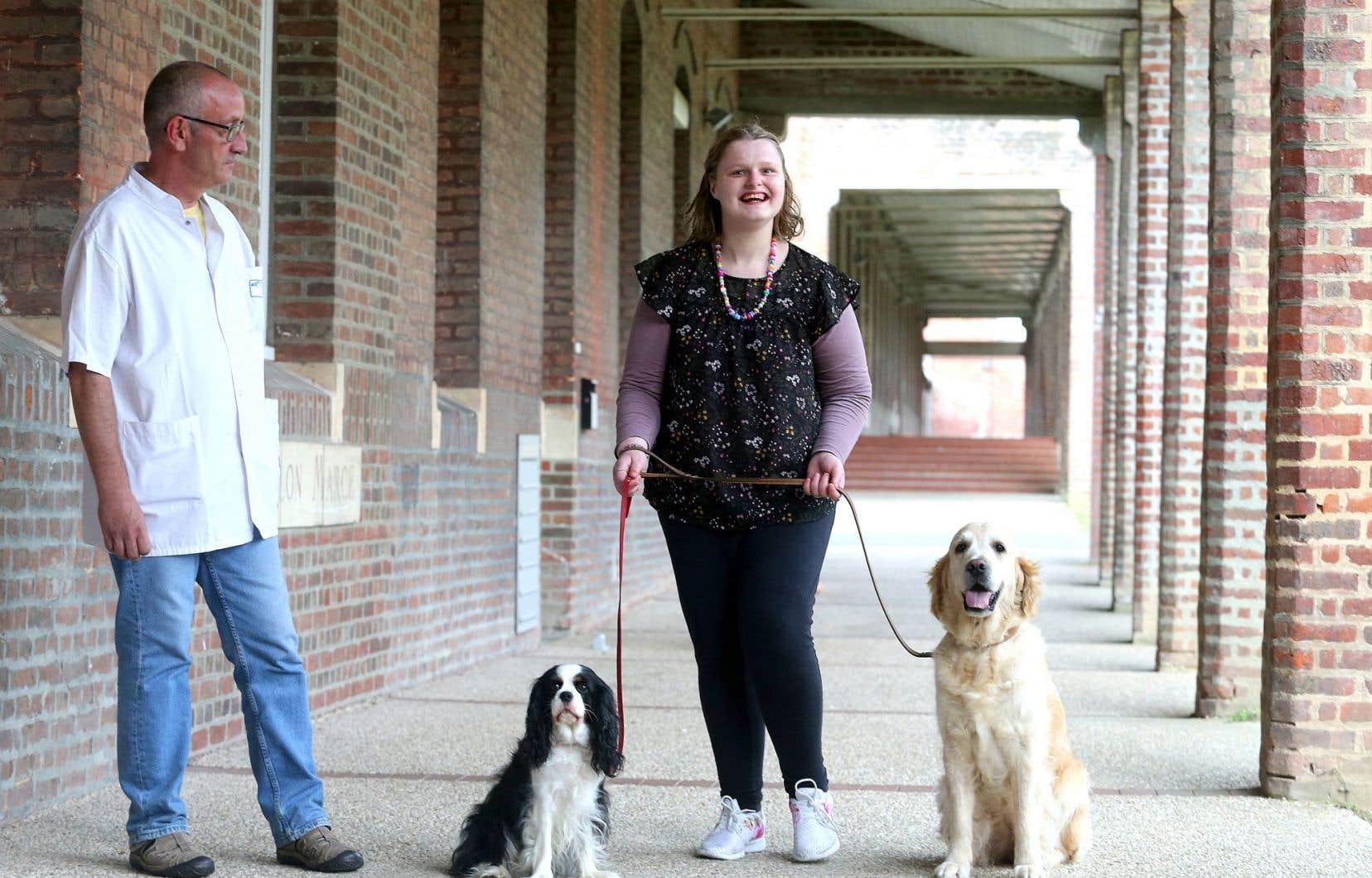 Priscillia, 27 ans, résidente de l'unité psychiatrique de l'hôpital Philippe Pinel d'Amiens, se promène avec deux chiens du cynothérapeute William Lambiotte (gauche).