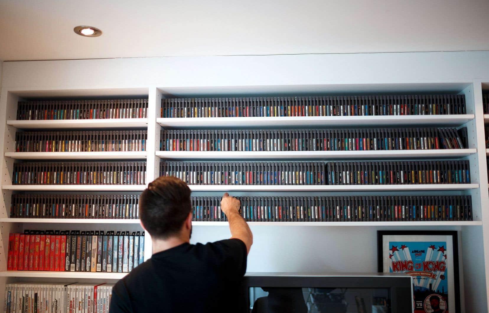 Une collection de près de 700 cassettes de NES, classées en ordre alphabétique, couvre un mur du salon du passionné des jeux vidéo surnommé Papa cassette.