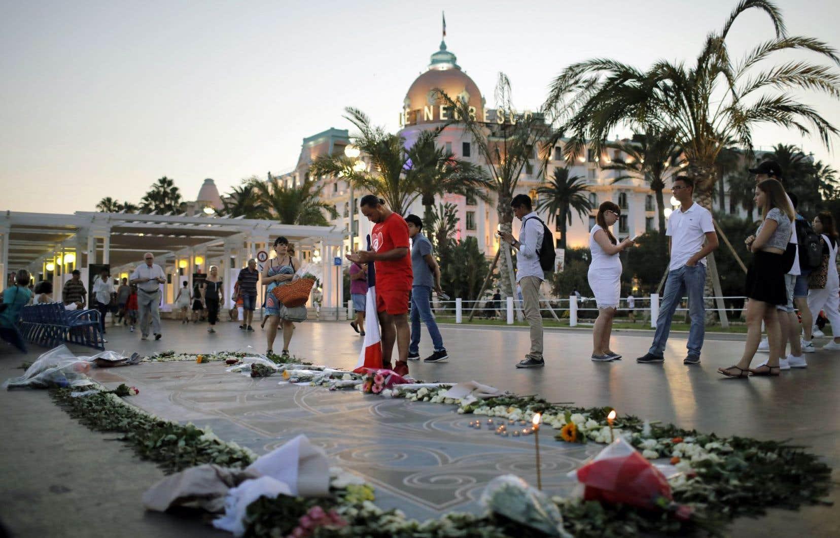 Un homme prie devant des fleurs et des bougies laissées en hommage aux victimes sur la promenade des Anglais, à Nice, vendredi.