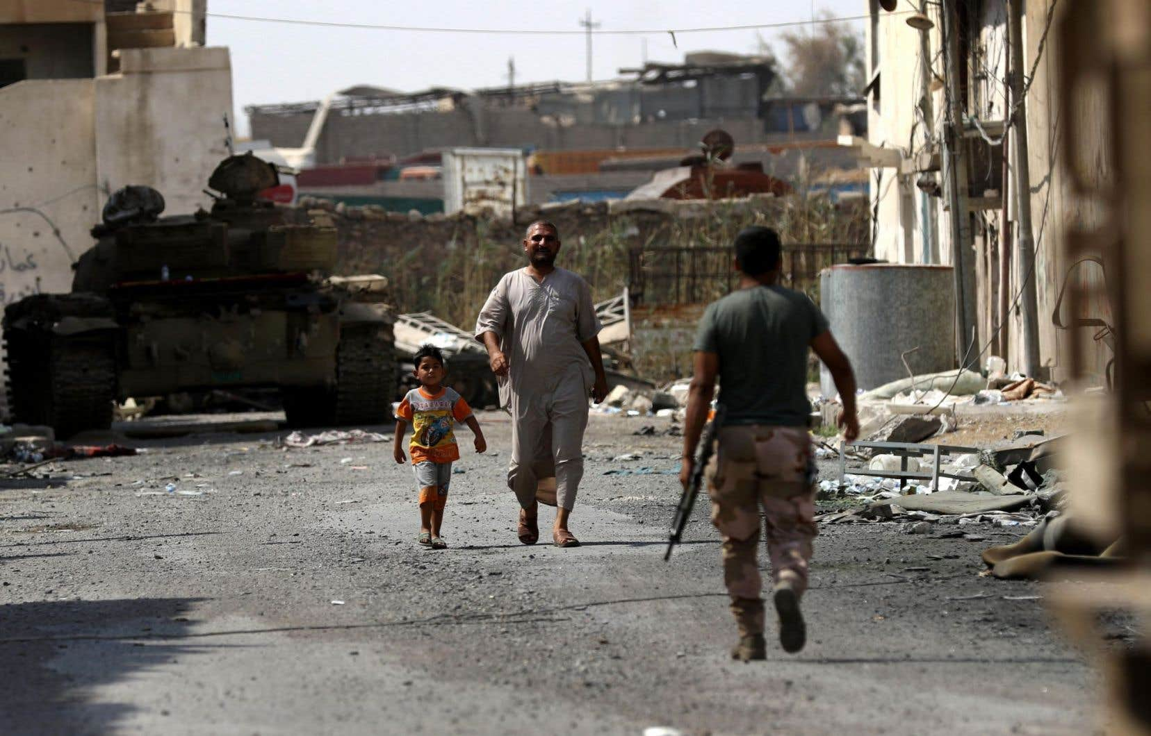Un membre des forces irakiennes patrouille dans une rue de l'ouest de Mossoul.