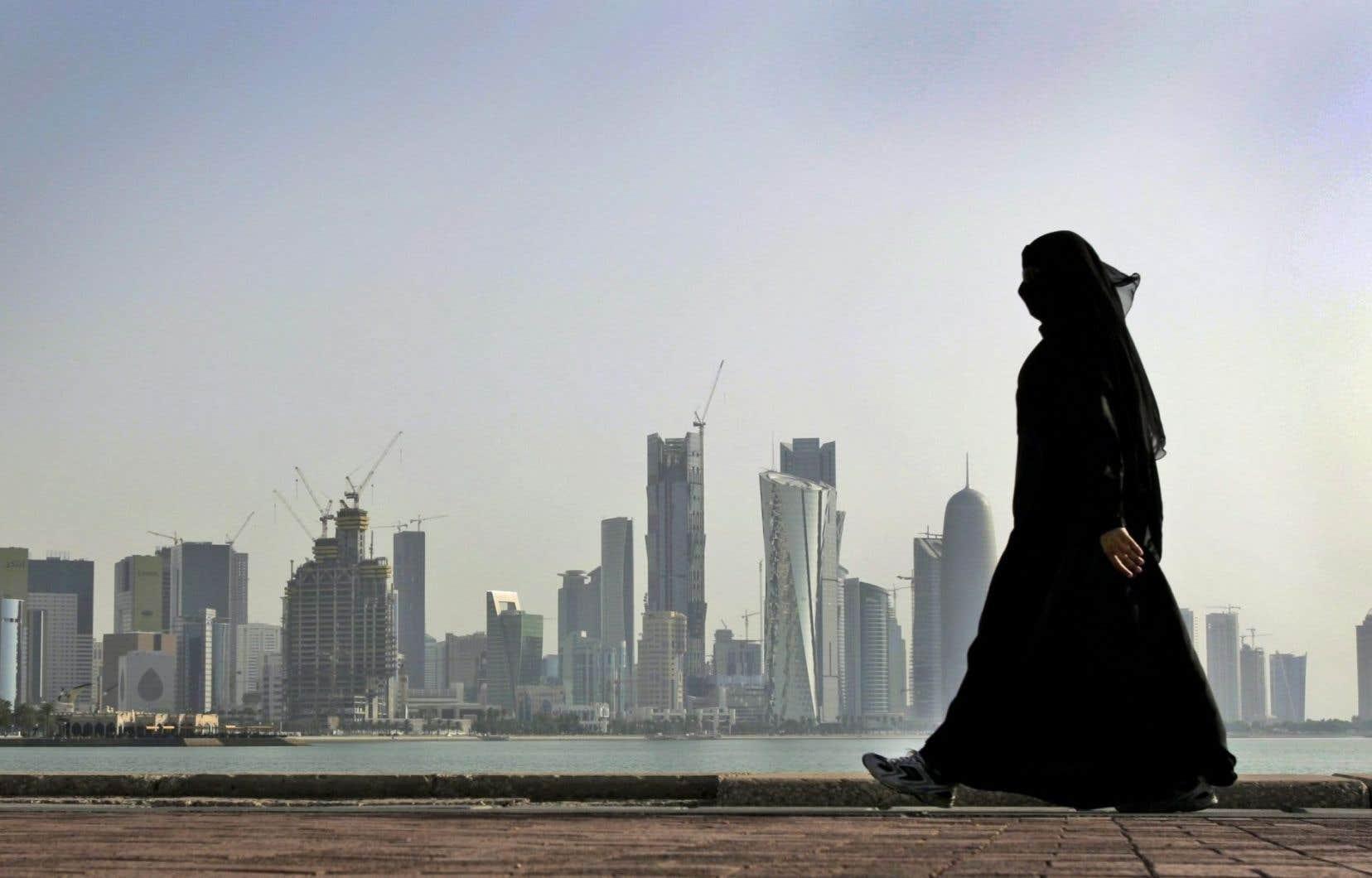 La ville de Dohase profile à l'horizon, derrière une femme qatarienne.