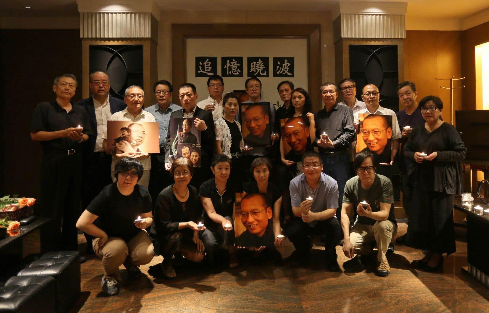 Des photos adressées à l'AFP montrent les amis du prix Nobel, emprisonné de 2008 jusqu'à sa mort, s'incliner face à une photo de Liu Xiaobo entourée de fleurs.<br />
