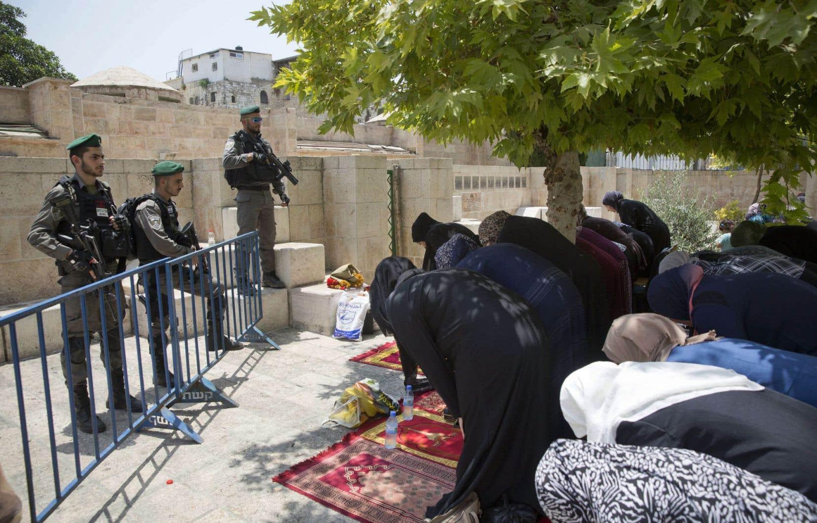 Des policiers israéliens montent la garde devant des femmes palestiniennes priant dans la vieille ville de Jérusalem.