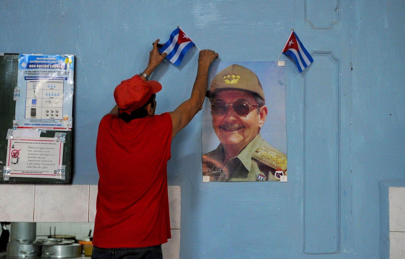 Sur son lieu de travail, un homme accroche un drapeau cubain à une photographie du président Raùl Castro, le 23 février 2017.