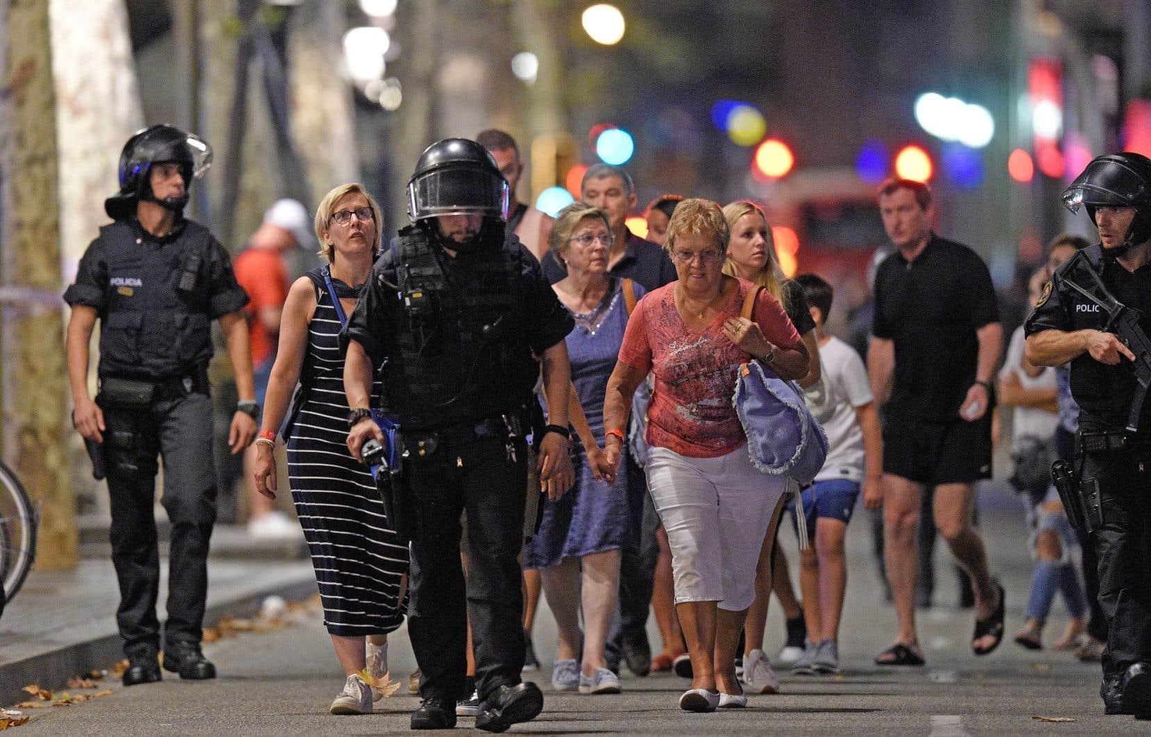 Des policiers escortent un groupe de clients d'un magasin du centre-ville touristique de Barcelone vers un endroit sécuritaire.