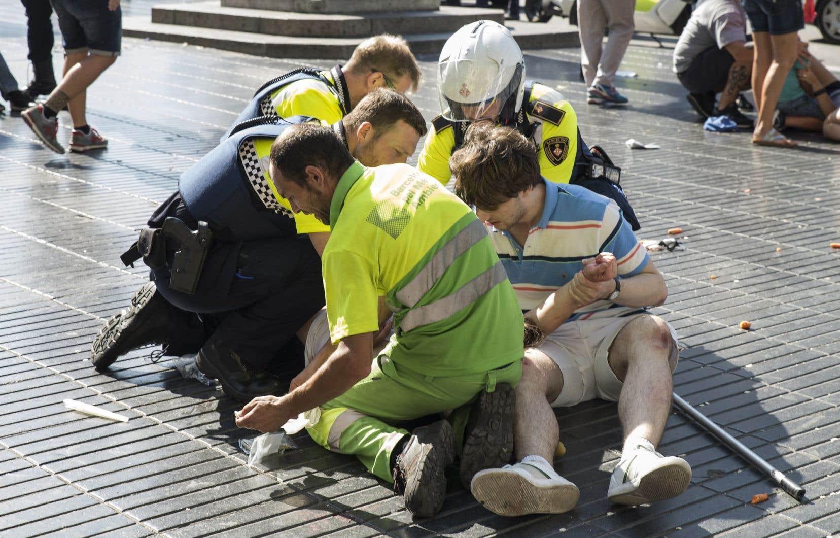 Un homme aide les policiers à porter secours à une victime.