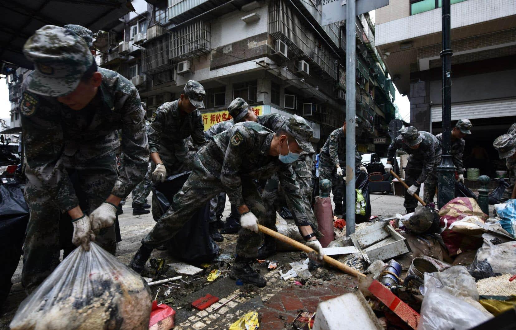 Des soldats de l'armée chinoise aident à éliminer les débris dand une rue à Macao.