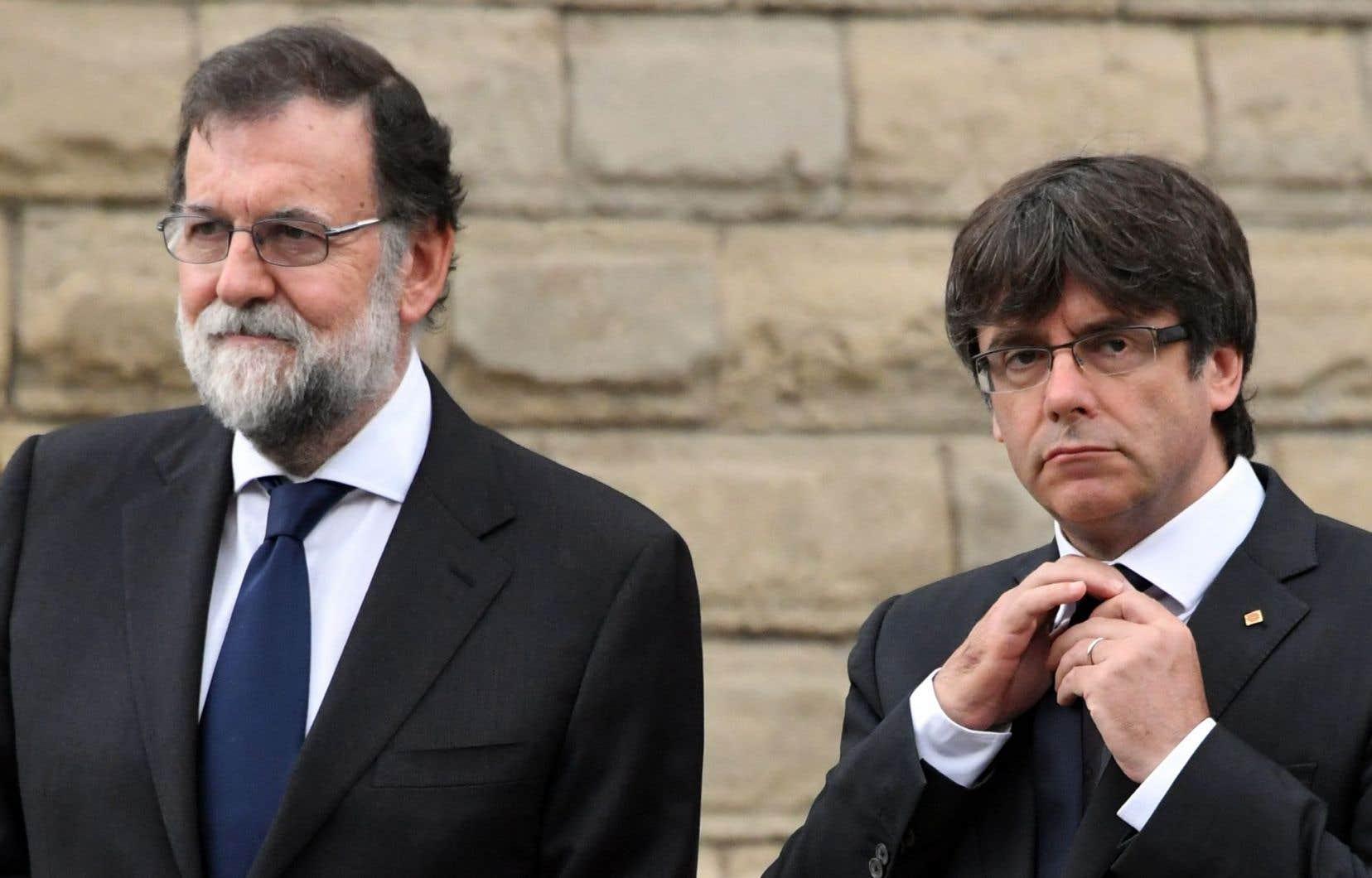 Le premier ministre espagnol, Mariano Rajoy (à gauche), aux côtés du président catalan, Carles Puigdemont, lors d'une cérémonie en hommage aux victimes des attentats de Catalogne, le 20 août.