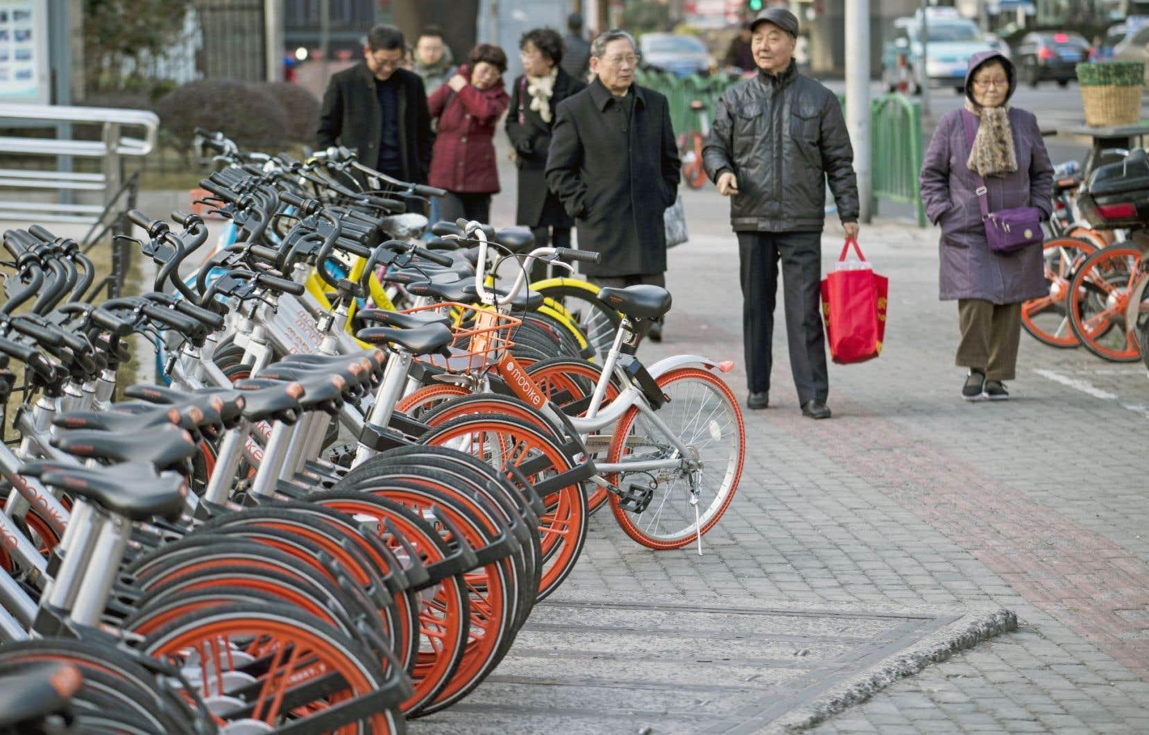 Des vélos aux couleurs des entreprises Mobike et Ofo sont stationnés dans une rue de Shanghai, en Chine.