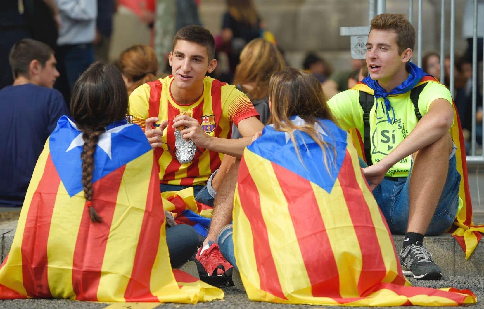 Des étudiants vêtus aux couleurs du drapeau des indépendantistes de la Catalogne, en marge d'une manifestation à Barcelone, vendredi