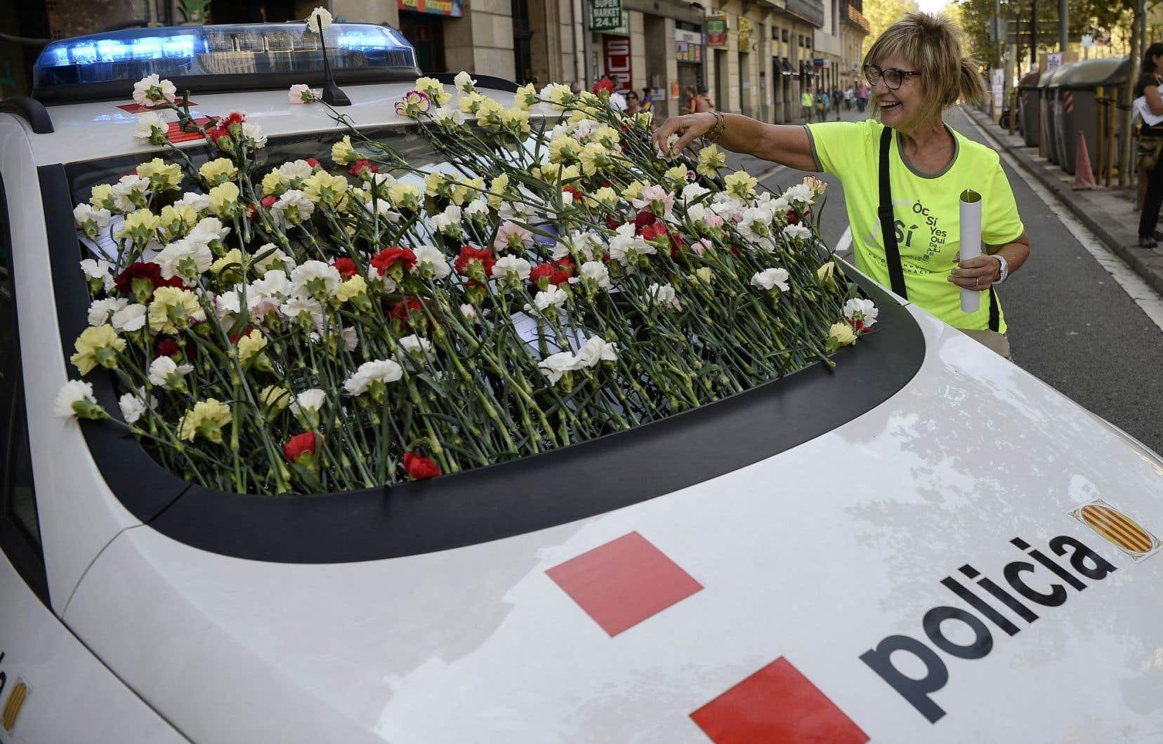 Une femme dépose des fleurs sur une voiture de la police catalane lors d'une manifestation pro-référendum, à Barcelone.