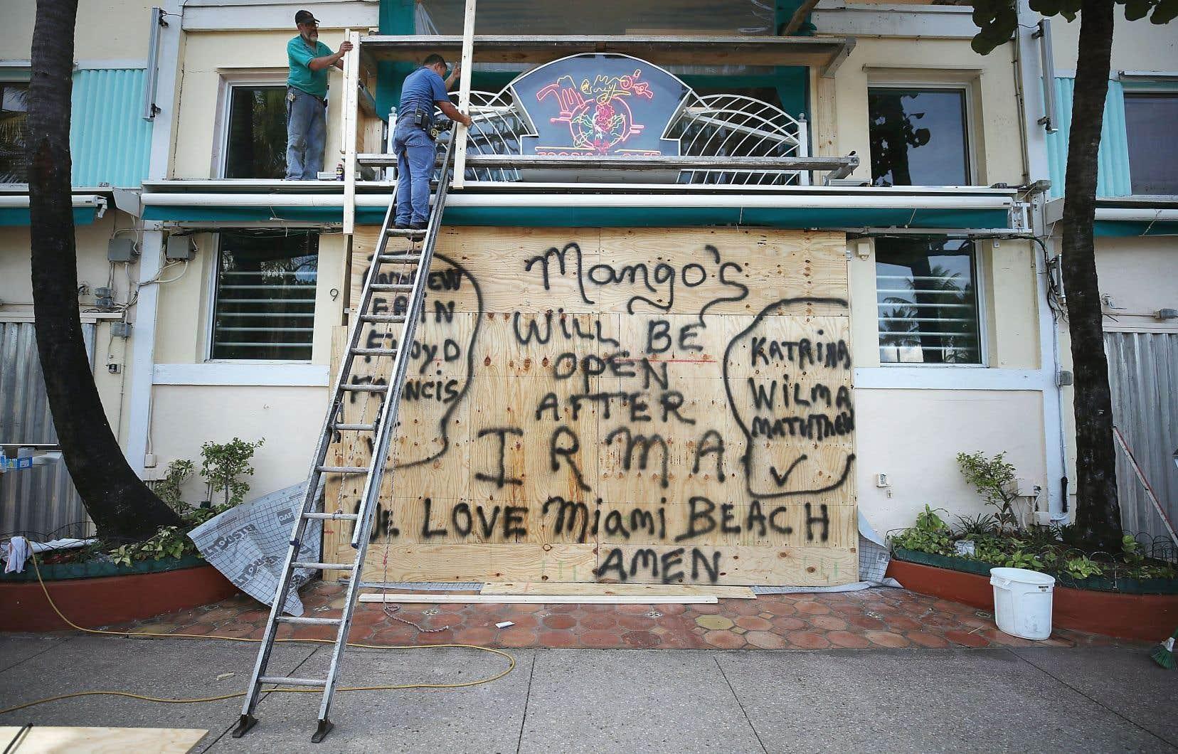 Des travailleurs ont barricadé un restaurant à Miami, en prévision de l'ouragan «Irma», au début septembre. Les pertes d'emplois se sont beaucoup fait ressentir dans l'industrie de la restauration.