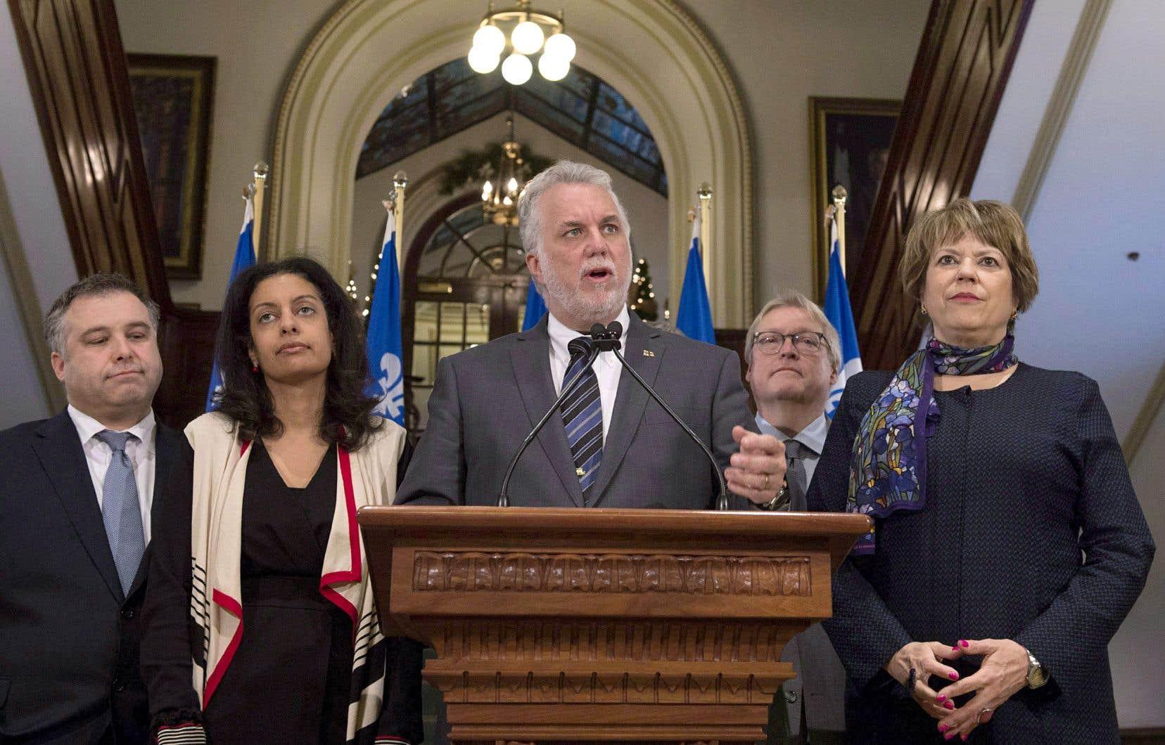 Le premier ministre Philippe Couillard entouré des ministres Sébastien Proulx, Dominique Anglade, Gaétan Barrette et Hélène David.